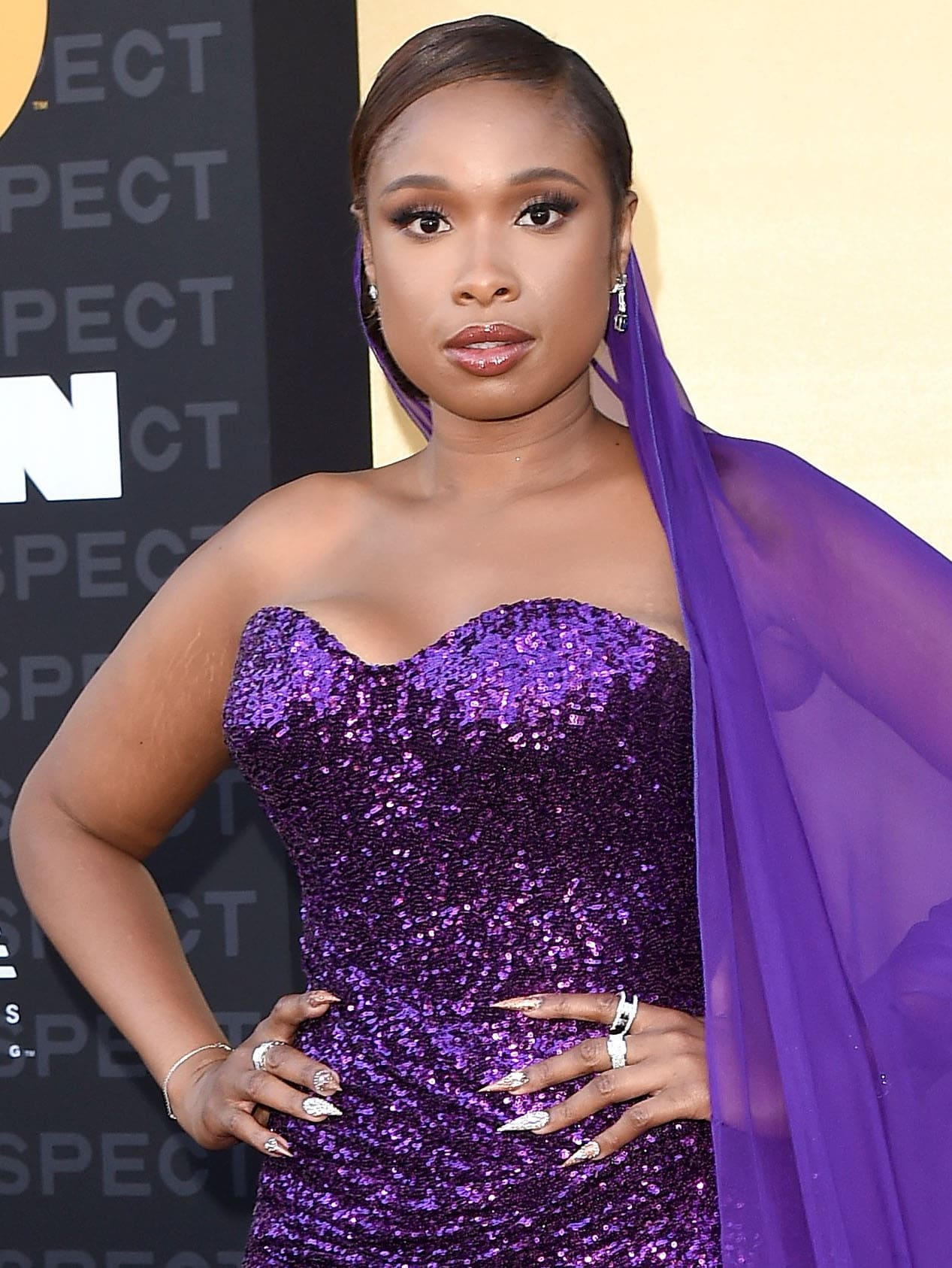 Jennifer Hudson styles her hair in a neat side-parted bun and wears neutral makeup with pink smokey eyeshadow