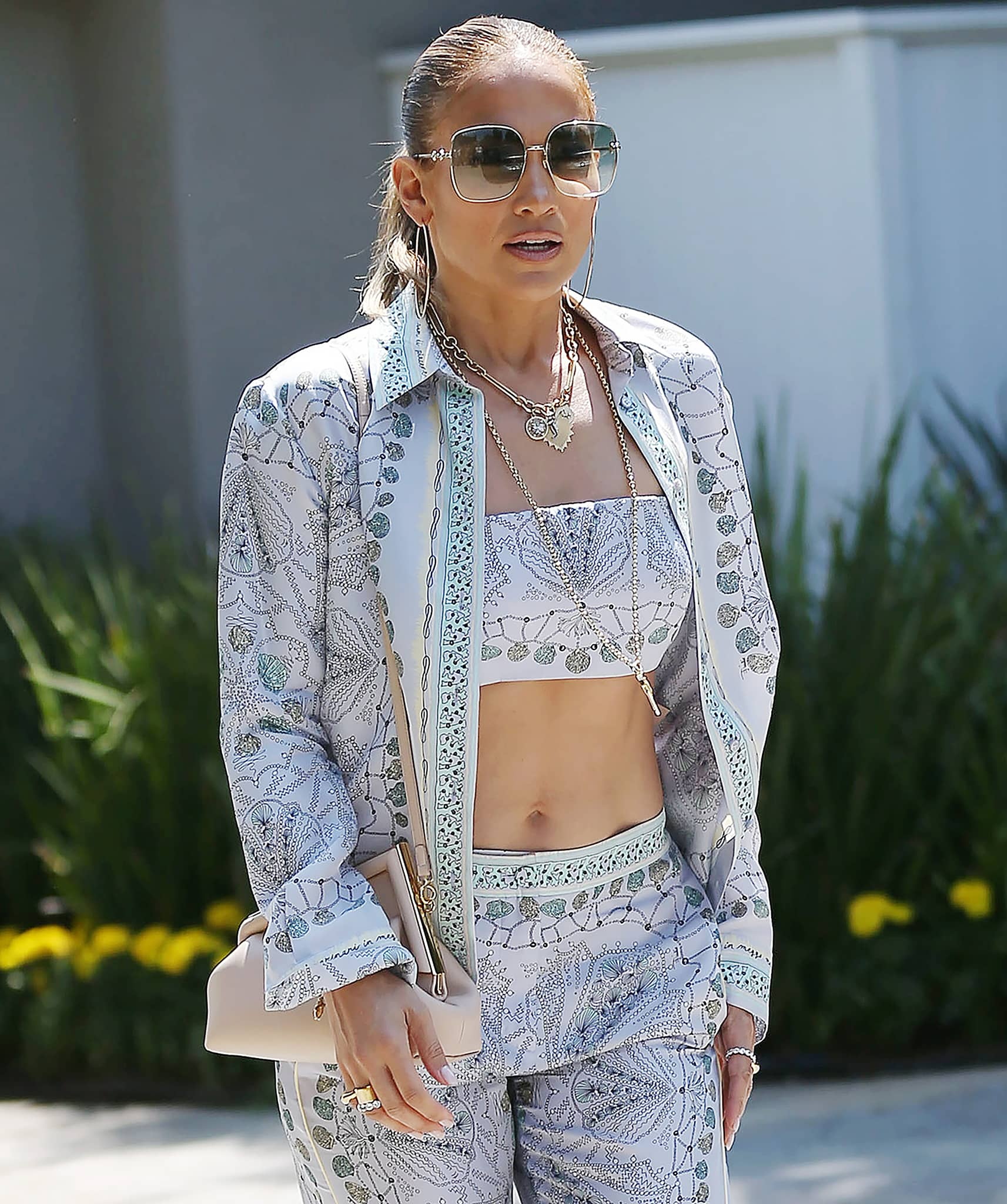 Jennifer Lopez slicks her hair back into a neat ponytail and accessorizes with Foundrae necklaces and Gucci sunglasses