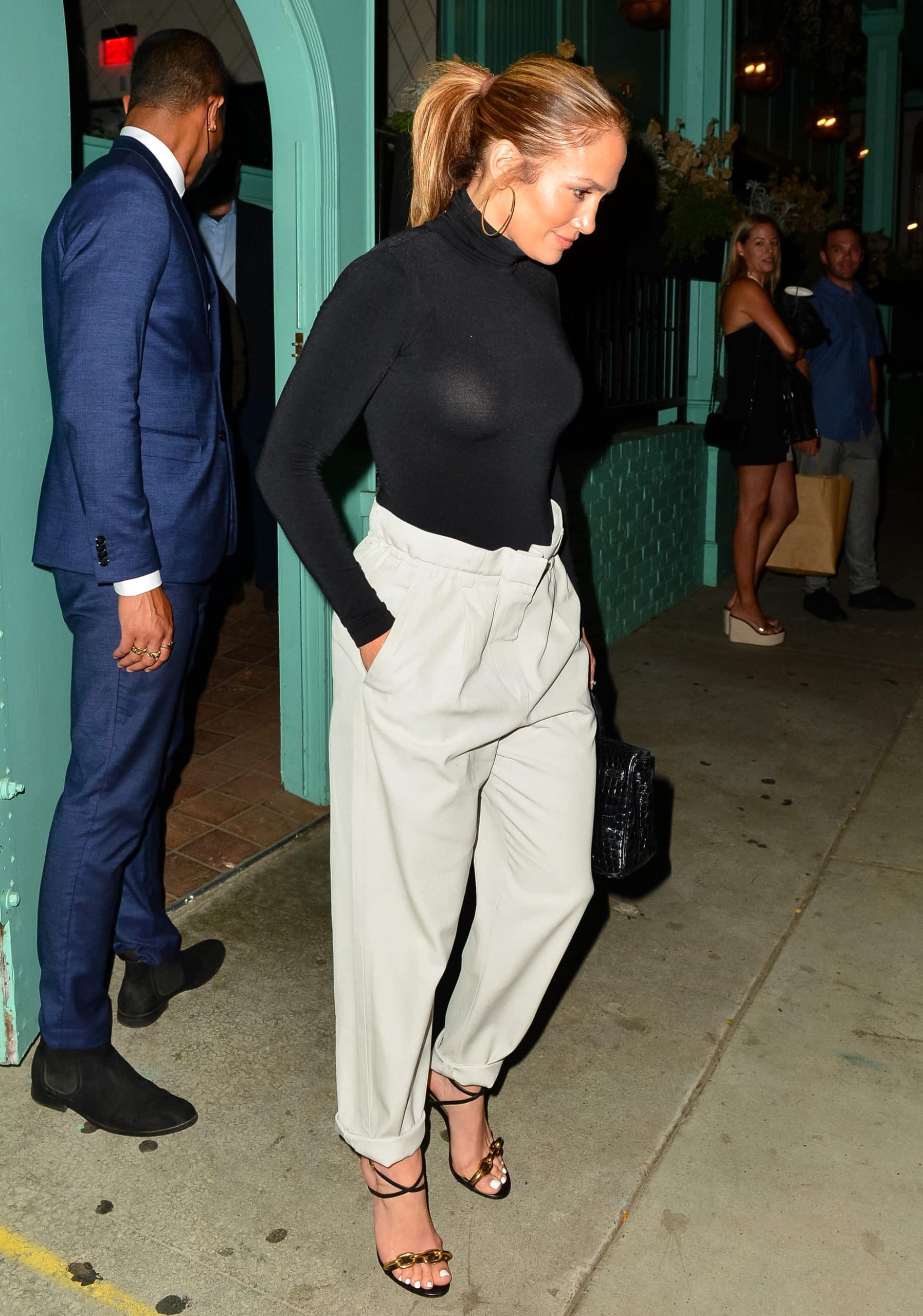 Jennifer Lopez wears a black Wolford bodysuit with paper bag trousers