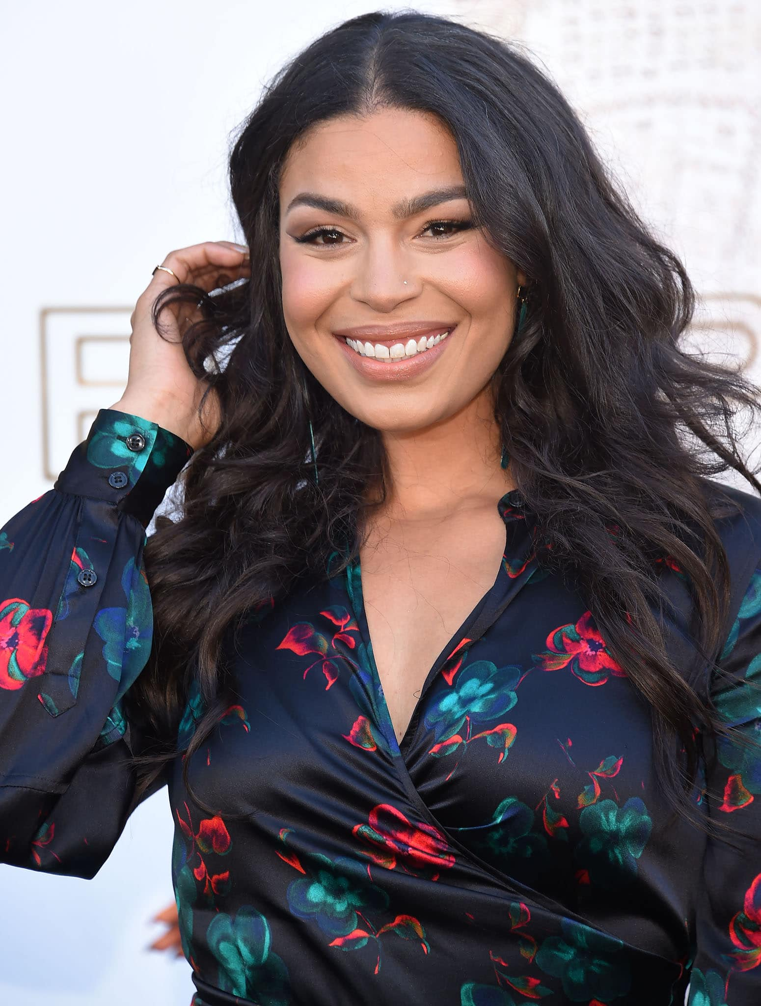 Jordin Sparks wears her long tresses in loose waves and highlights her features with nude makeup