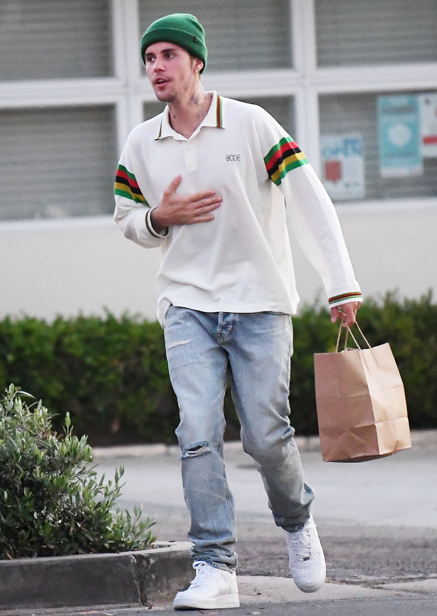 Justin Bieber shows off his cool street style with a long-sleeved polo shirt, light-washed jeans, green beanie, and Nike shoes