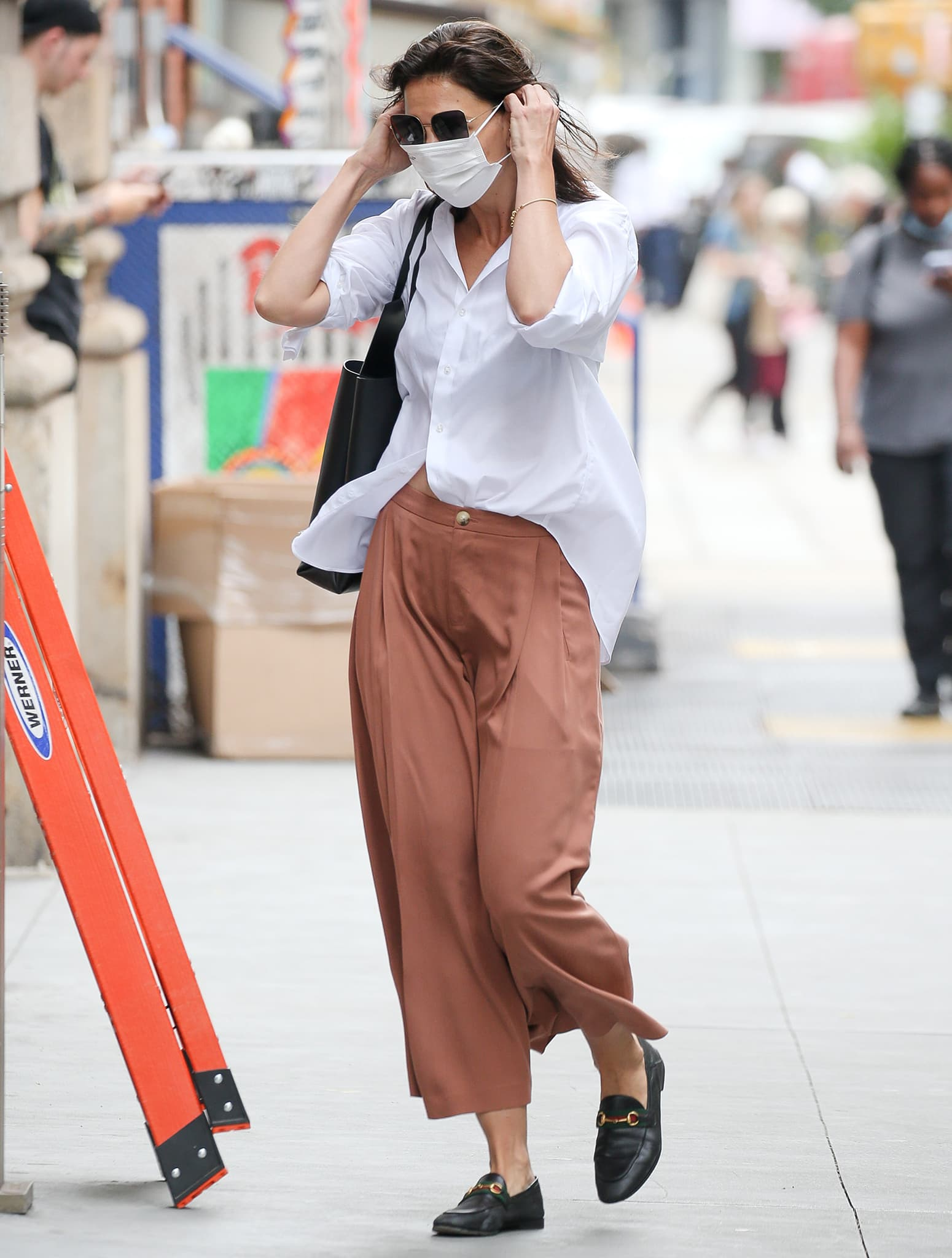 Showing to do the French tuck shirt style trick from Queer Eye, Katie Holmes steps out in New York City