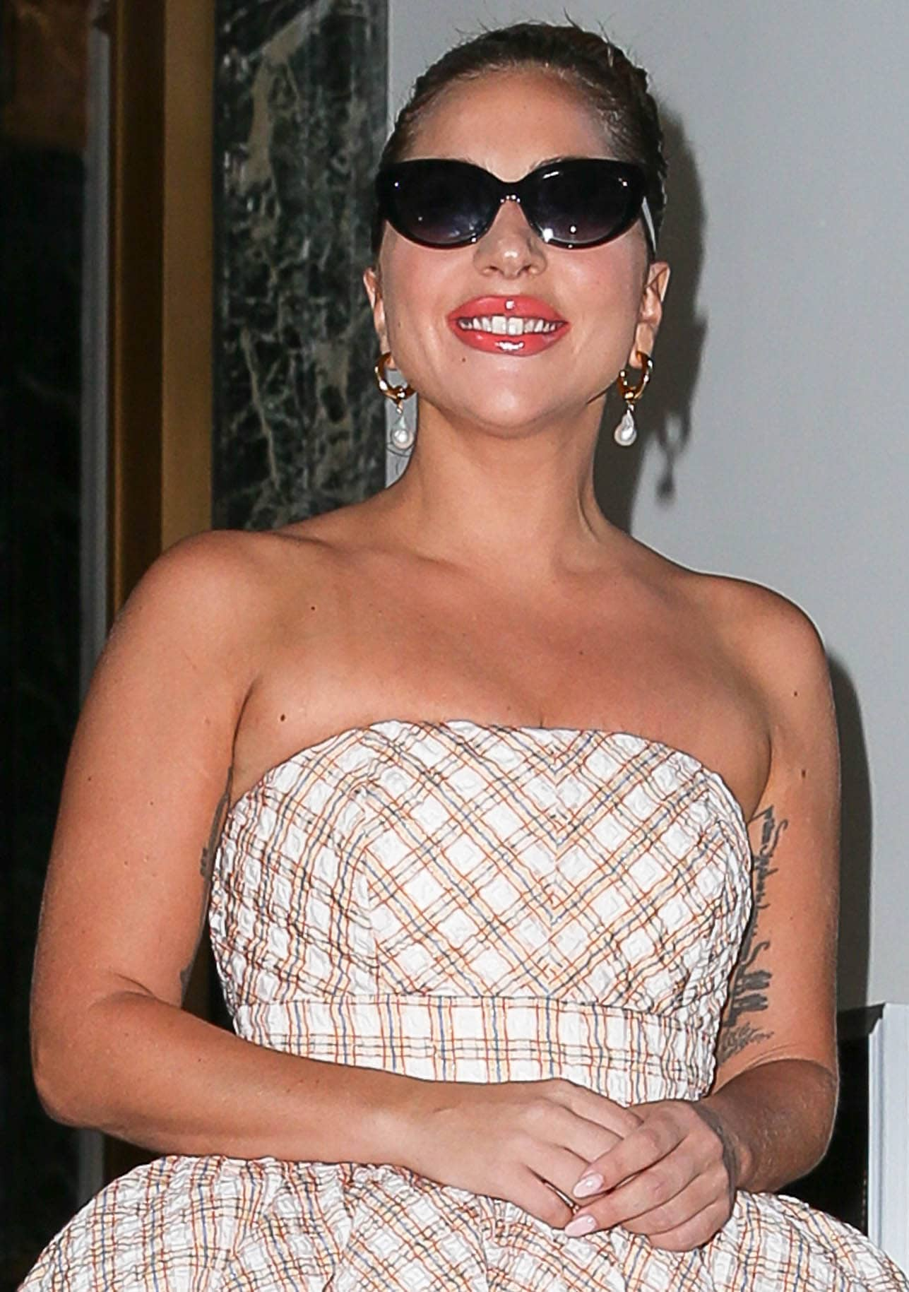 Lady Gaga accessorizes with pearl drop earrings and glams up further with a high bun and red lip gloss