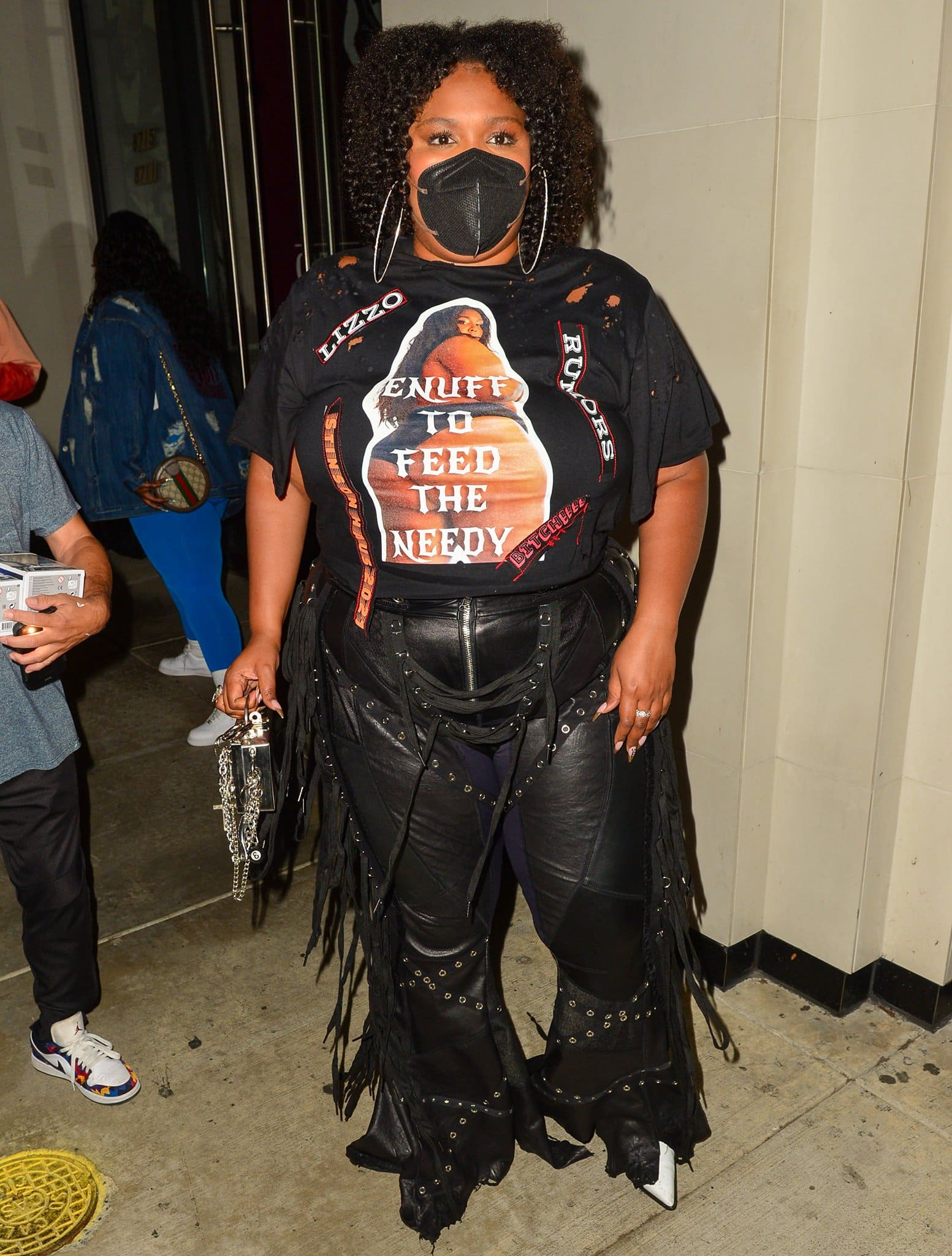 Lizzo wears a pair of fringed leather pants with a black tee printed with her bikini photo on front