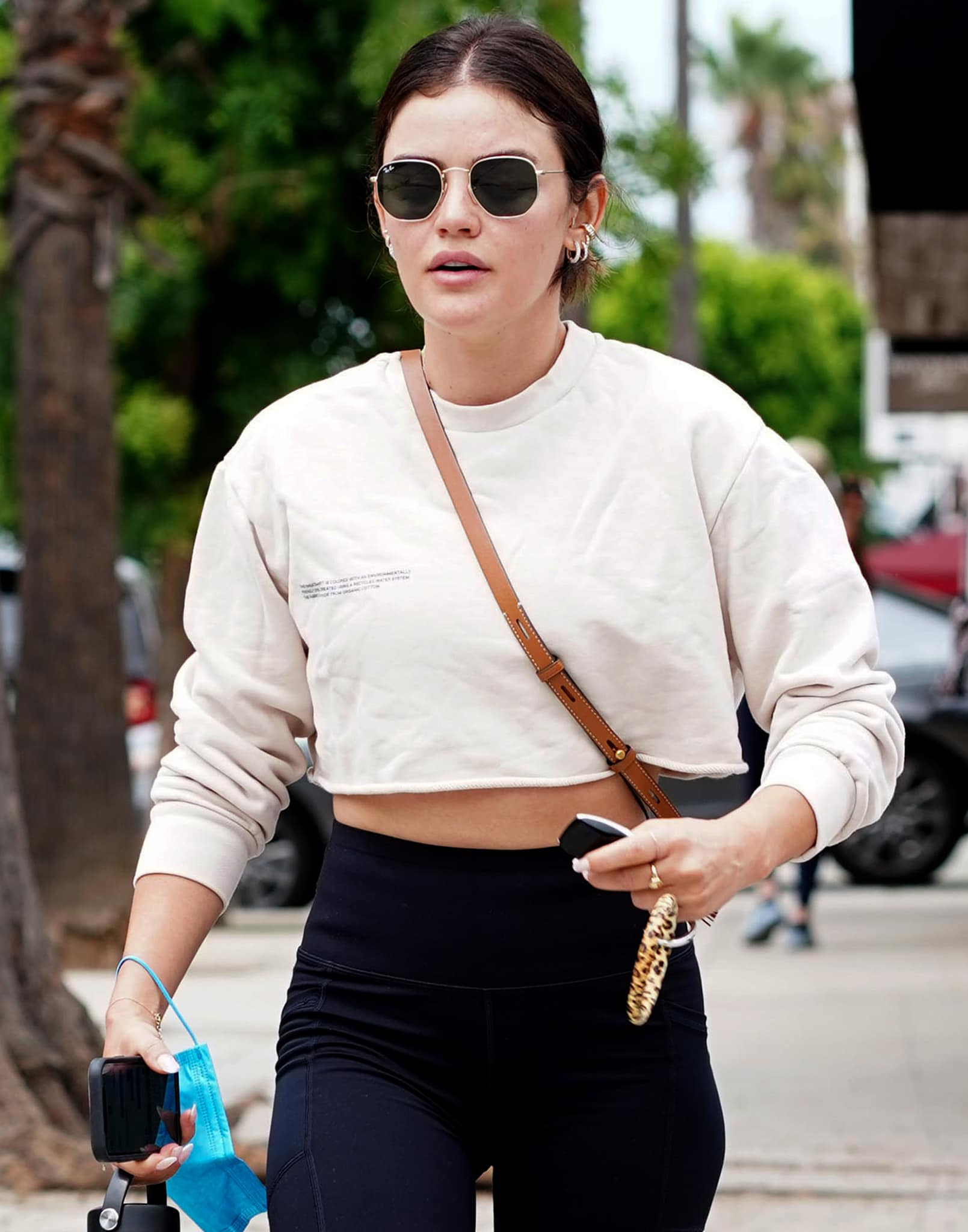 Lucy Hale wears a casual ponytail with a hint of lip color as she hides her eyes behind her RayBan sunglasses