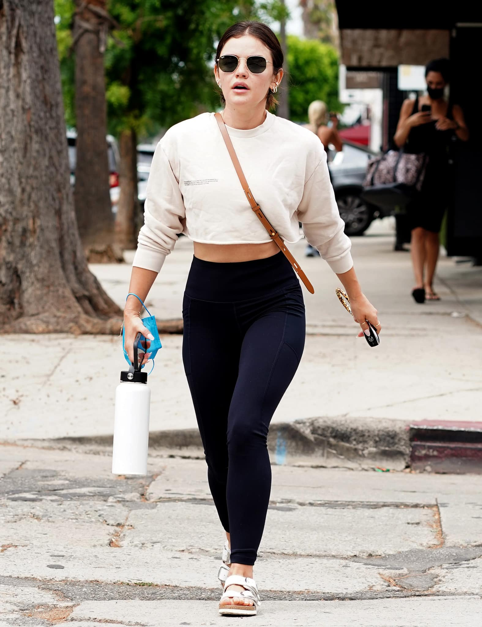 Lucy Hale shows a glimpse of midriff in a Pangaia cropped sweatshirt and a pair of leggings on August 19, 2021