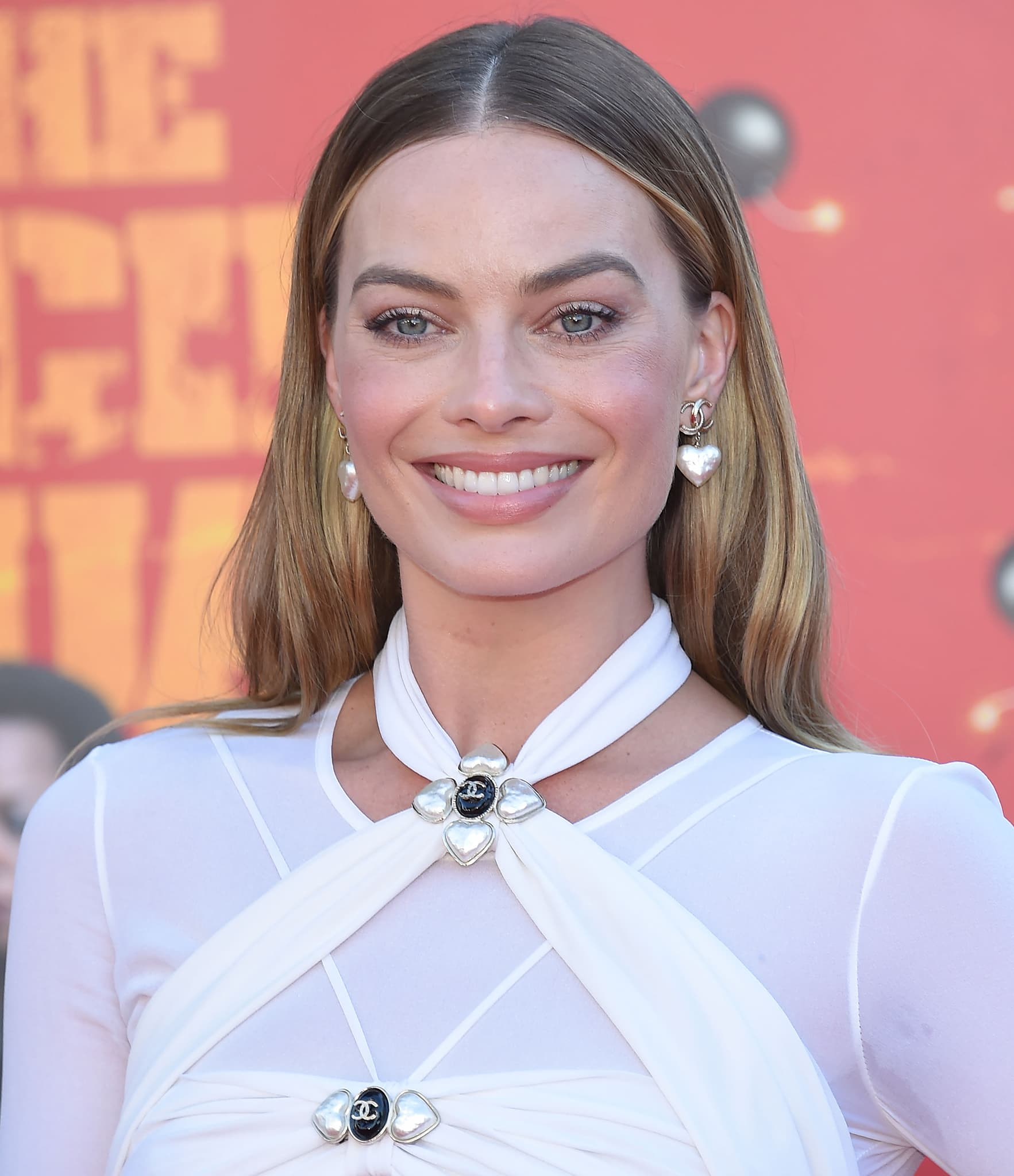 Margot Robbie wears her signature soft makeup look and styles her hair straight with a center parting