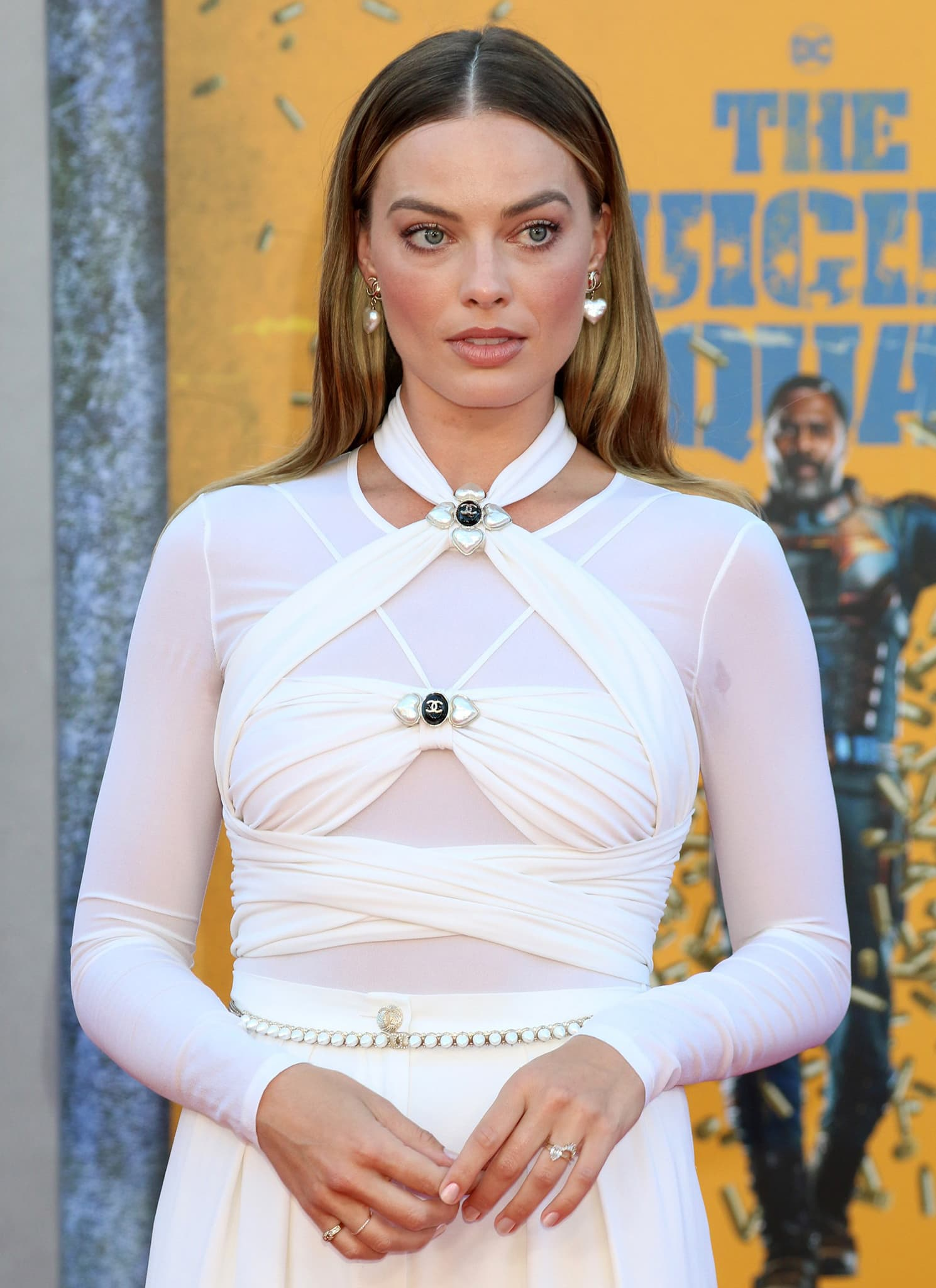 Margot Robbie wears a sheer long-sleeved top underneath a wraparound halter top with Chanel pearl emblems