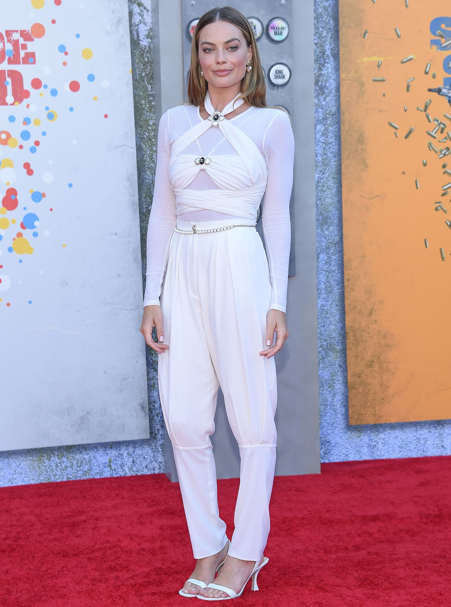 Margot Robbie pairs her white top with Chanel tapered white pants styled with a pearl-embellished chain belt