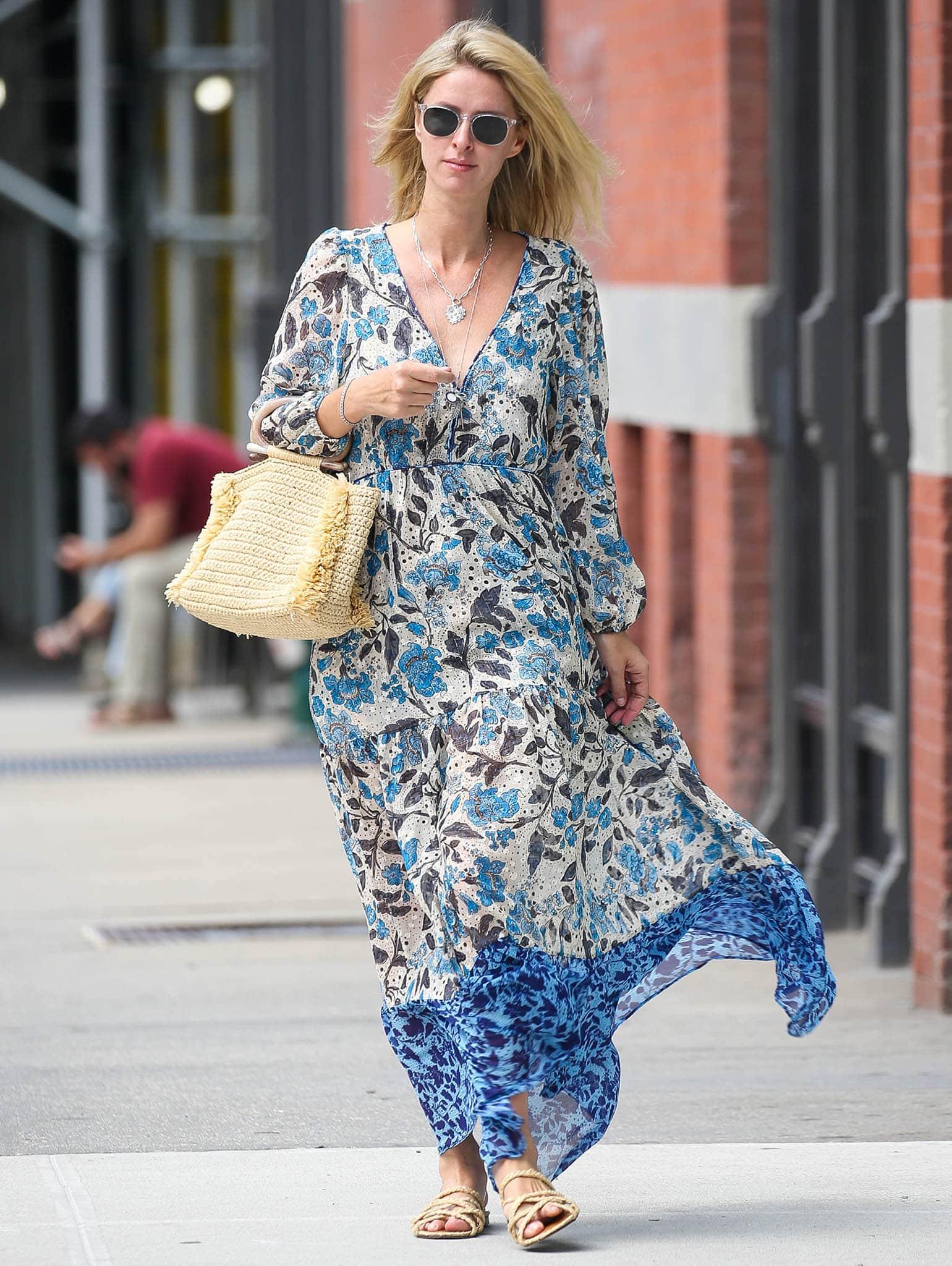Nicky Hilton teams her Misa LA blue floral maxi dress with a Carolina Santa Domingo raffia tote