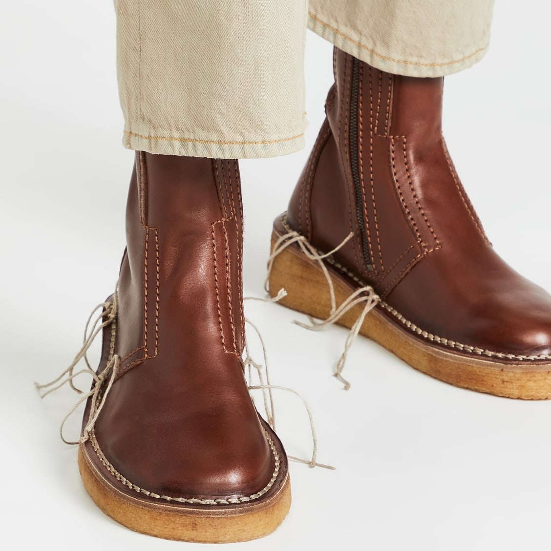 Acne Studios' brown leather Bura boots featuring distressed welt stitching with exaggerated threads