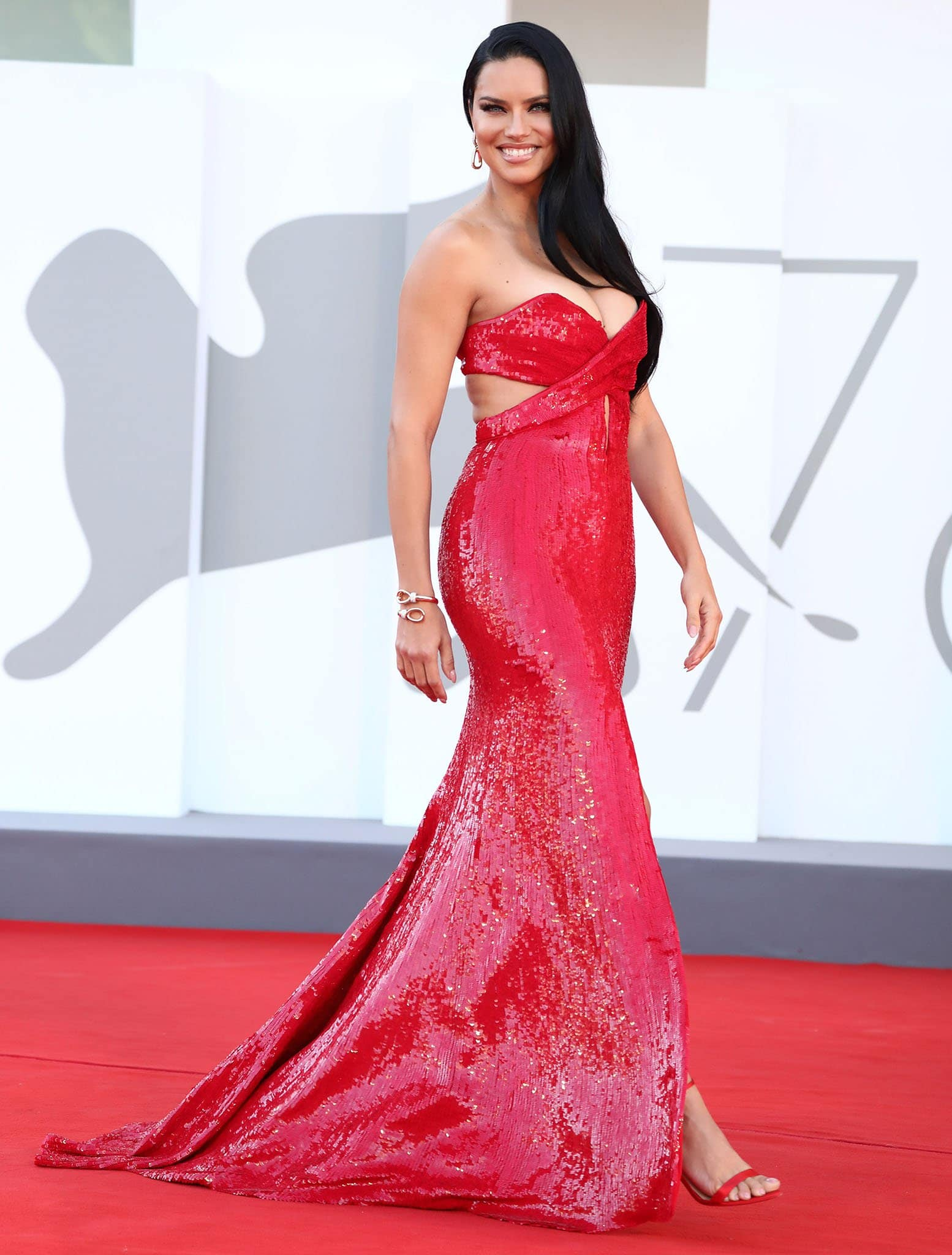 Adriana Lima looks sensational in her red sequined gown from Etro