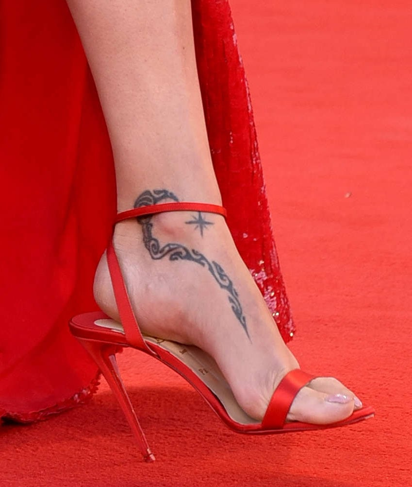 Adriana Lima shows off her foot tattoo in Christian Louboutin 514 red satin heels