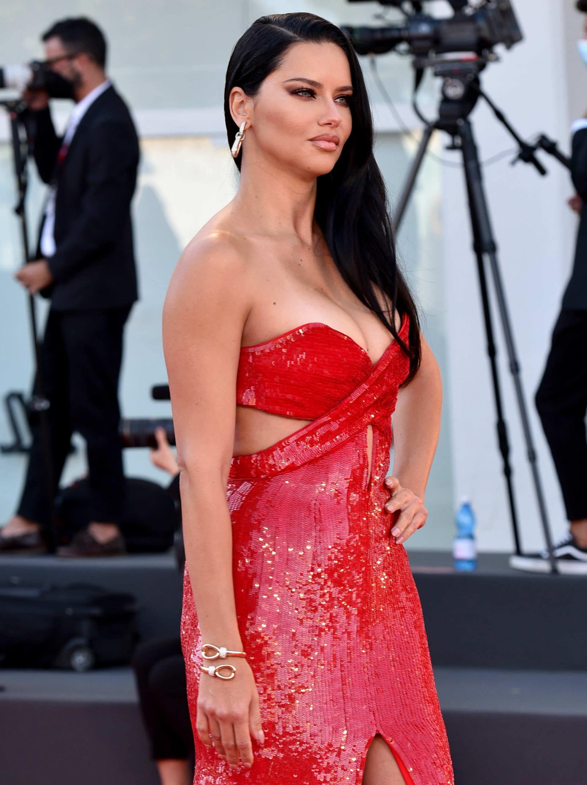 Adriana Lima wears side-parted loose waves with smokey eyeshadow and red bottom eyeliner
