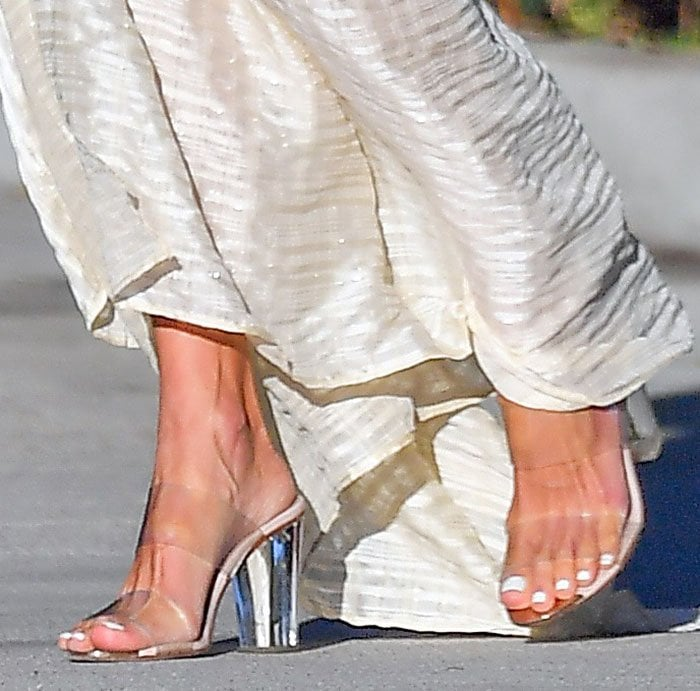 Alessandra Ambrosio completes her boho princess look by showing off her feet in clear two-strap mules with lucite heels