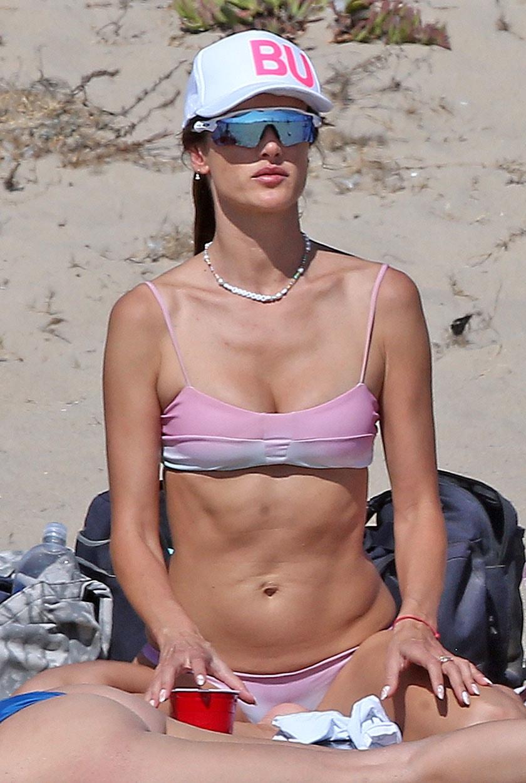 Alessandra Ambrosio wears a Fancy Lids BU white trucker cap and Oakley Radar sunglasses