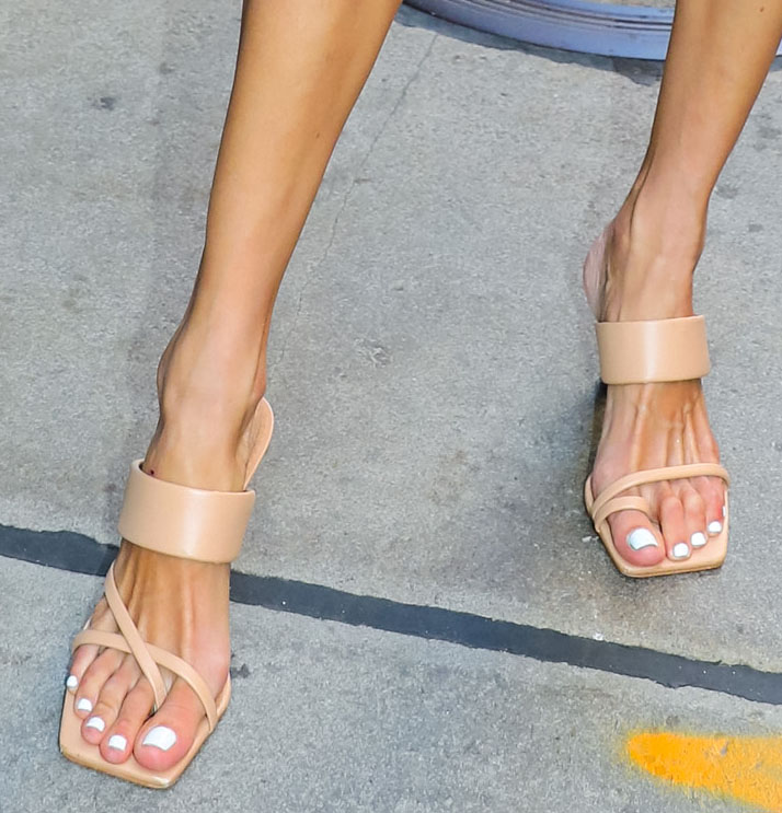 Alessandra Ambrosio shows off her feet and white pedicure in tan square-toe slide sandals