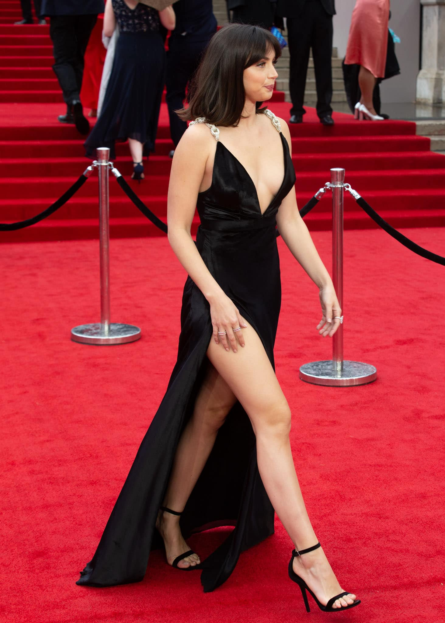 Ana de Armas puts on a leggy display in her Louis Vuitton dress featuring risqué hip-high slit and plunging neckline