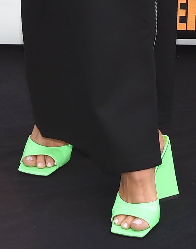 Bebe Rexha adds color to her black outfit by showing off her feet in green square-toe sandals