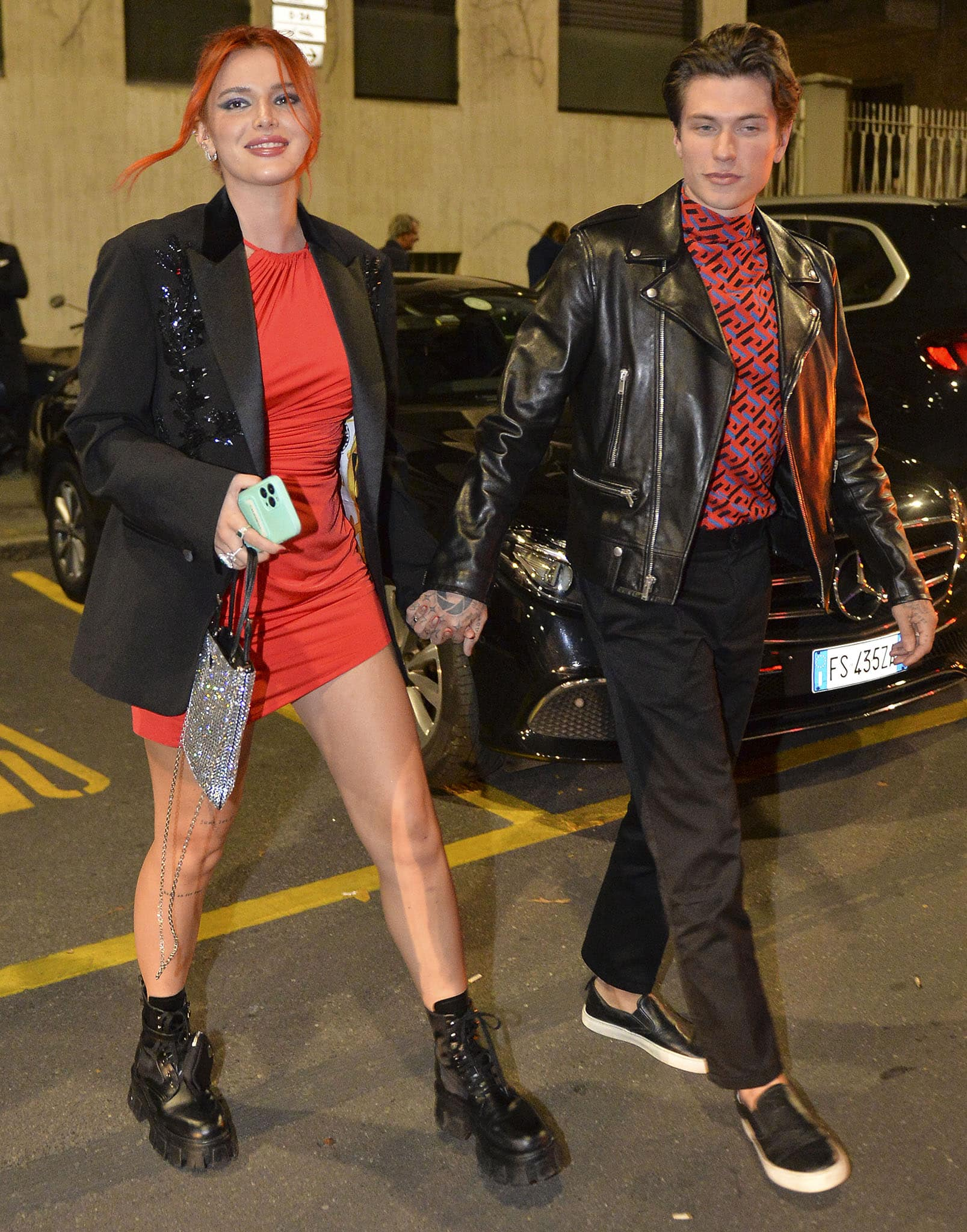 Bella Thorne parades her legs in a red mini dress with a black tuxedo, while Benjamin coordinates with Bella in a red Versace top with a black leather biker jacket