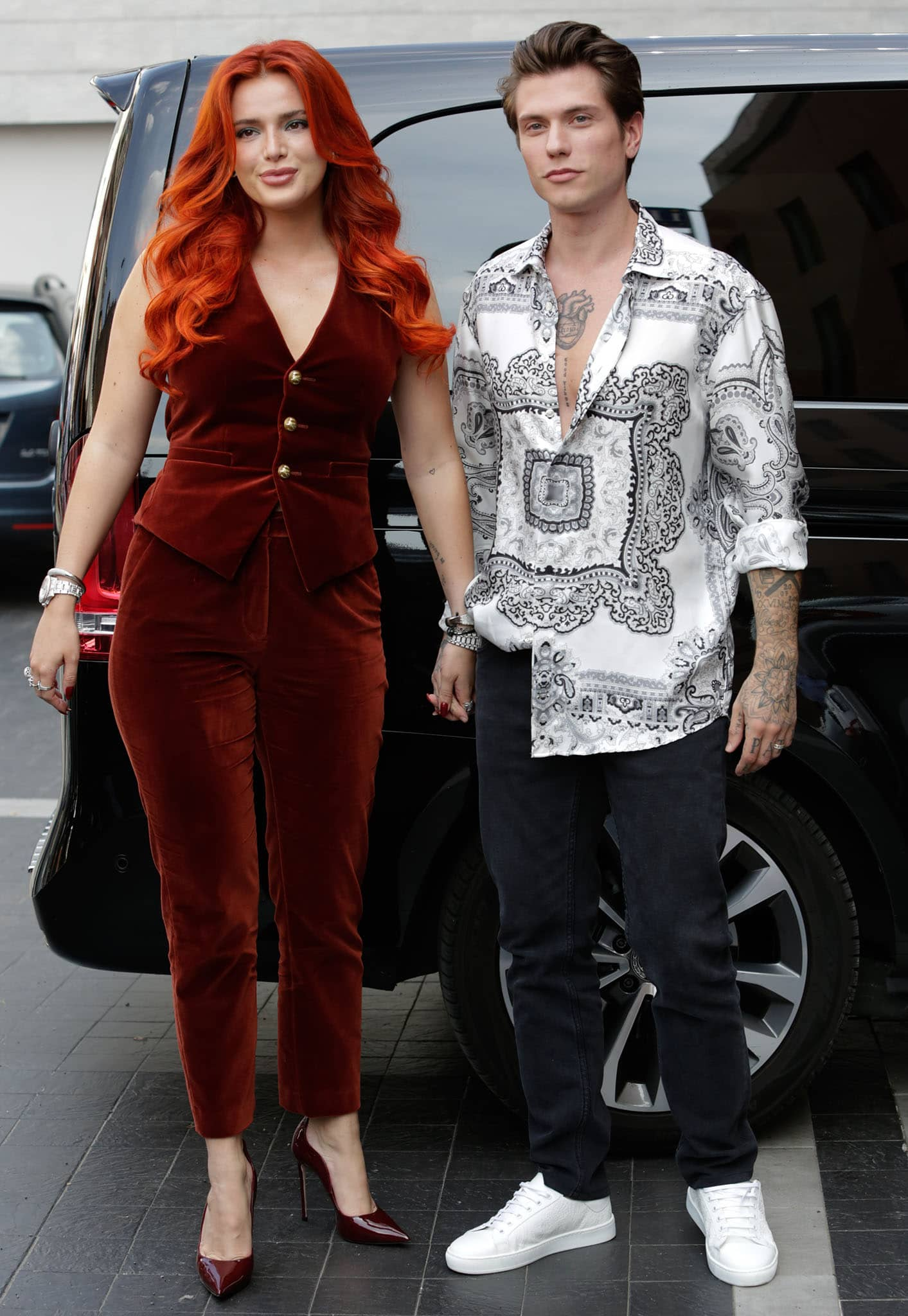 Bella Thorne highlights her figure in an Etro red velvet vest top and cigarette pants, while Benjamin opts for a black-and-white paisley-print shirt with black jeans