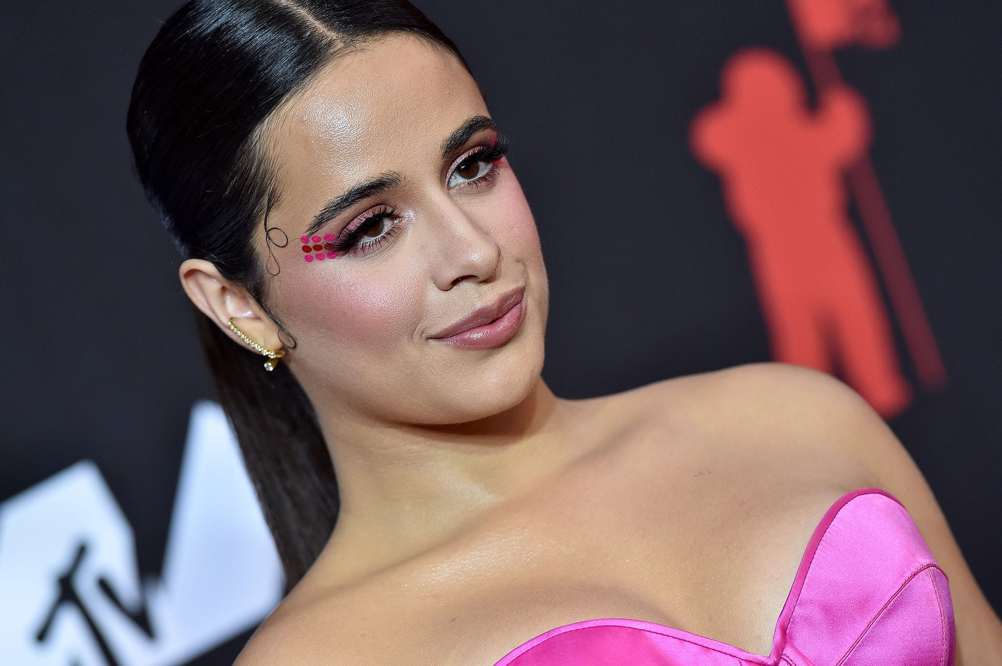 Camila Cabello wears a long, center-parted ponytail and bold makeup with colorful dots on the corner of her eyes