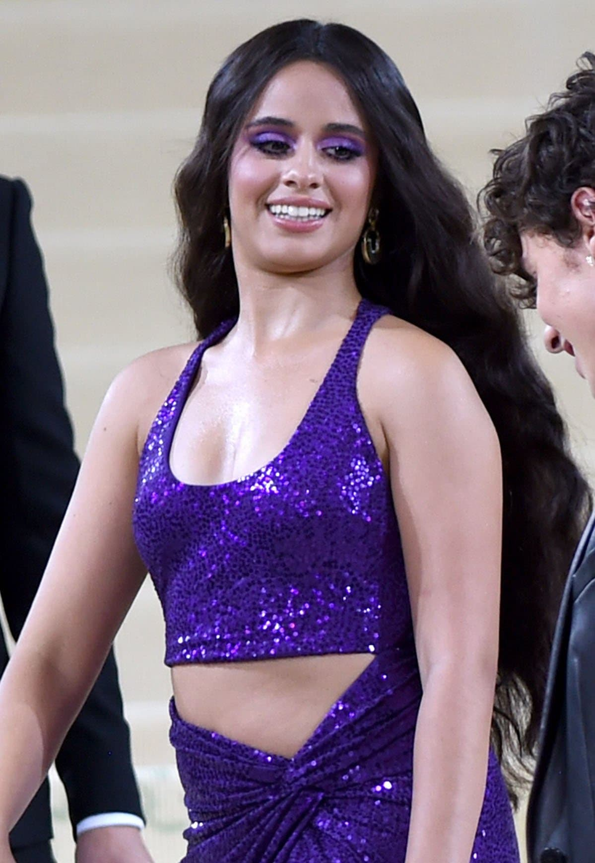 Camila Cabello matches her purple eyeshadow with her outfit and wears her long hair in thick waves