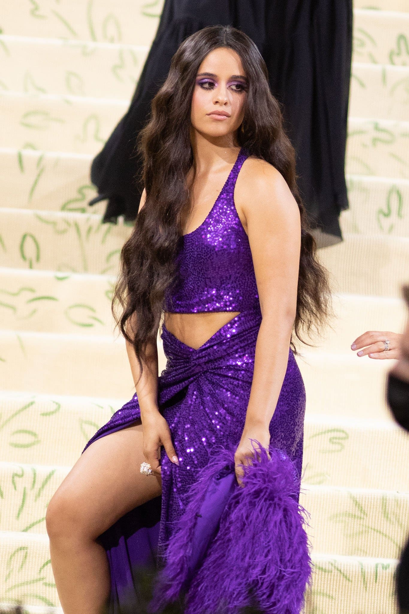 Camila Cabello accessorizes with David Webb jewelry and carries a purple clutch