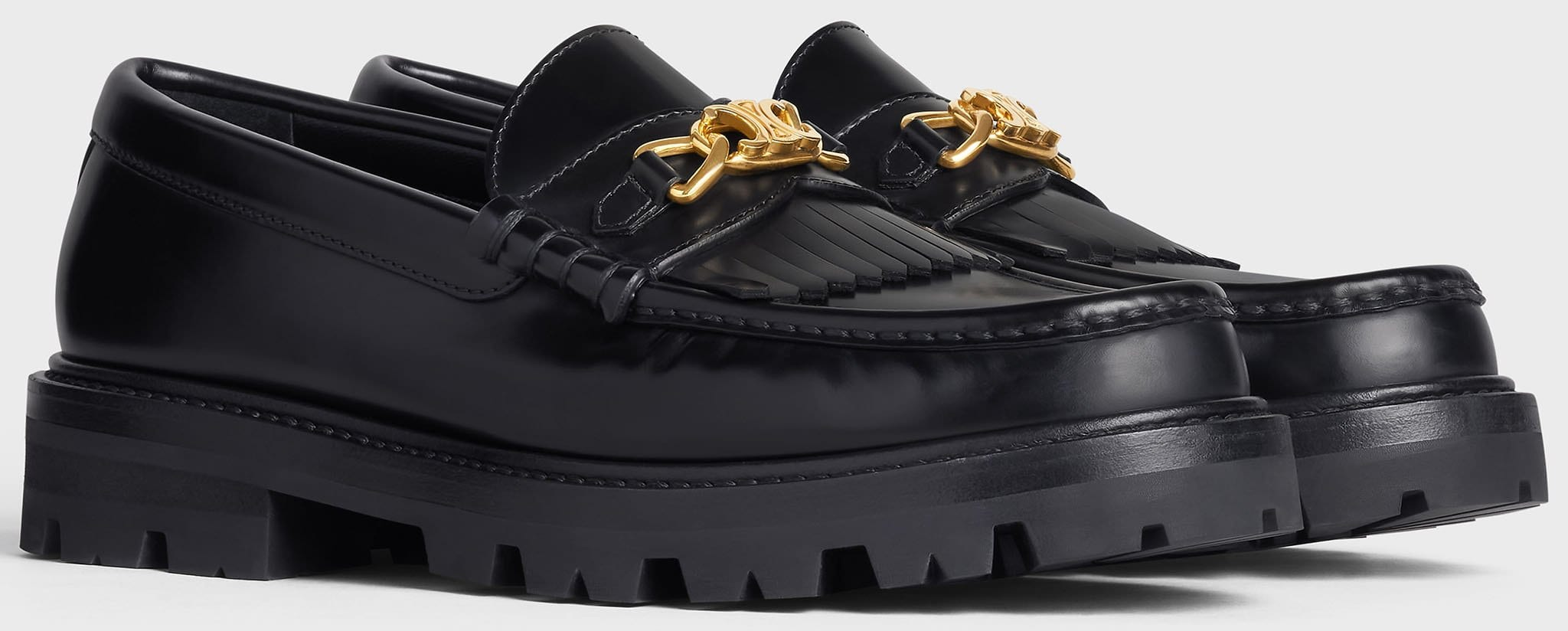 The Celine Margaret chunky loafers feature Triomphe gold chain, fringes, and rubber lug outsoles
