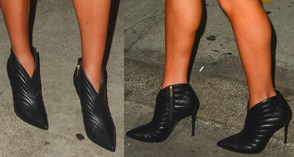 Olivia Culpo wears black smooth quilted leather boots featuring a notched trim and pointy toe