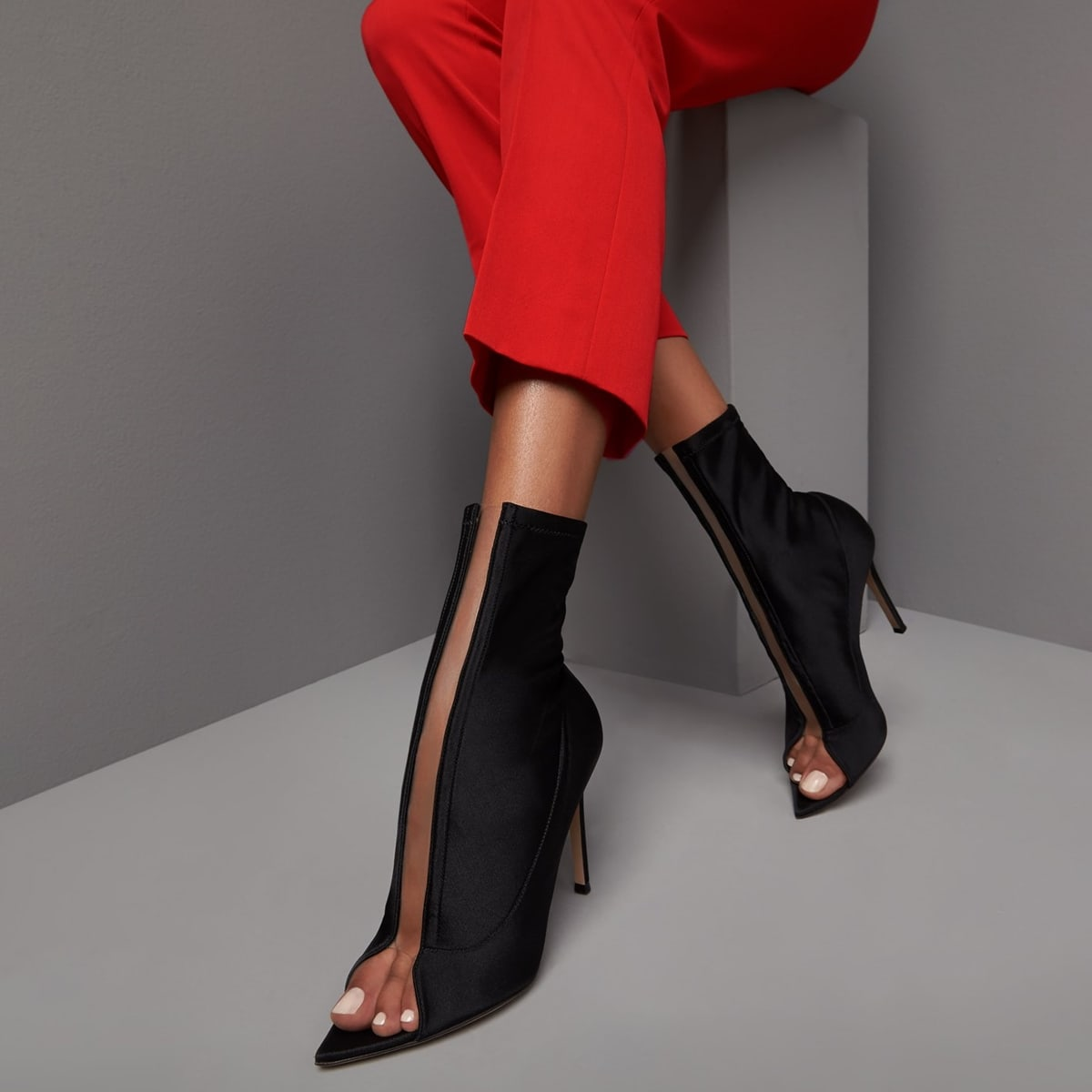 Cut from a stretch material, these black booties feature a rubber panel creating a cutout illusion