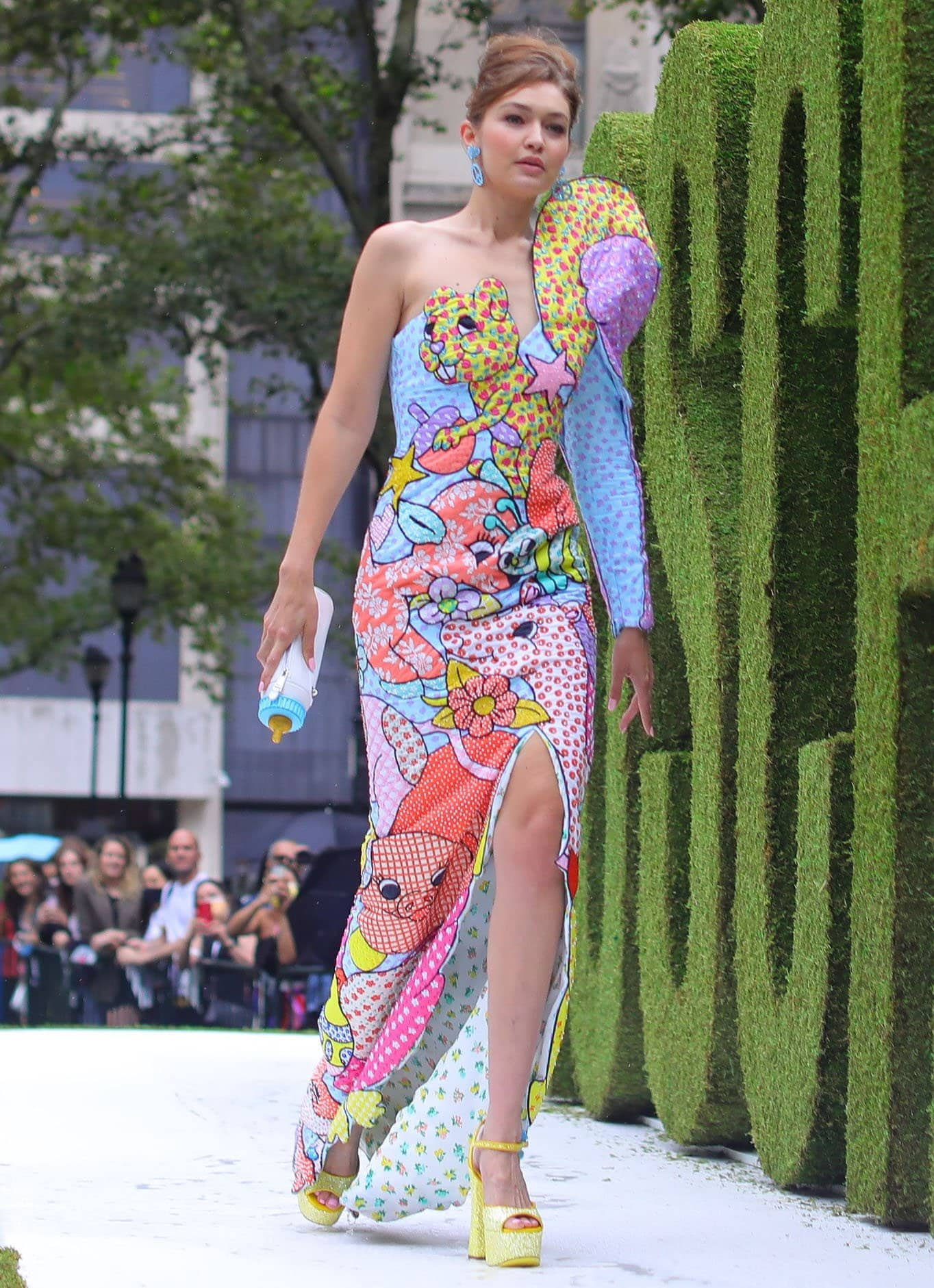 Gigi Hadid wears a pastel cartoon animal frock with yellow platform heels and a baby bottle clutch for Moschino's NYFW runway show on September 9, 2021