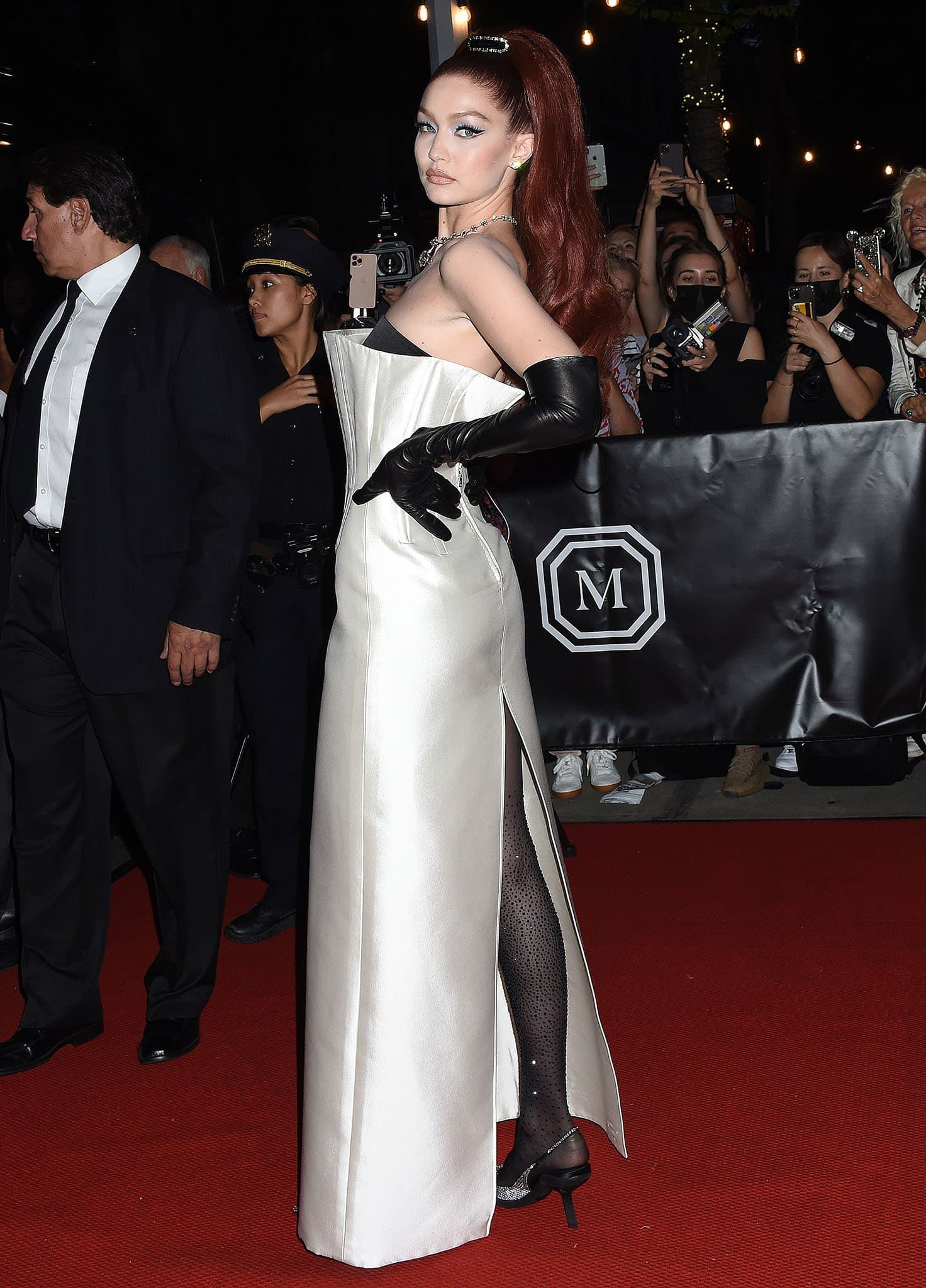 With her red hair high up in a retro-inspired ponytail, Gigi Hadid shows off her curves in a custom Prada column gown