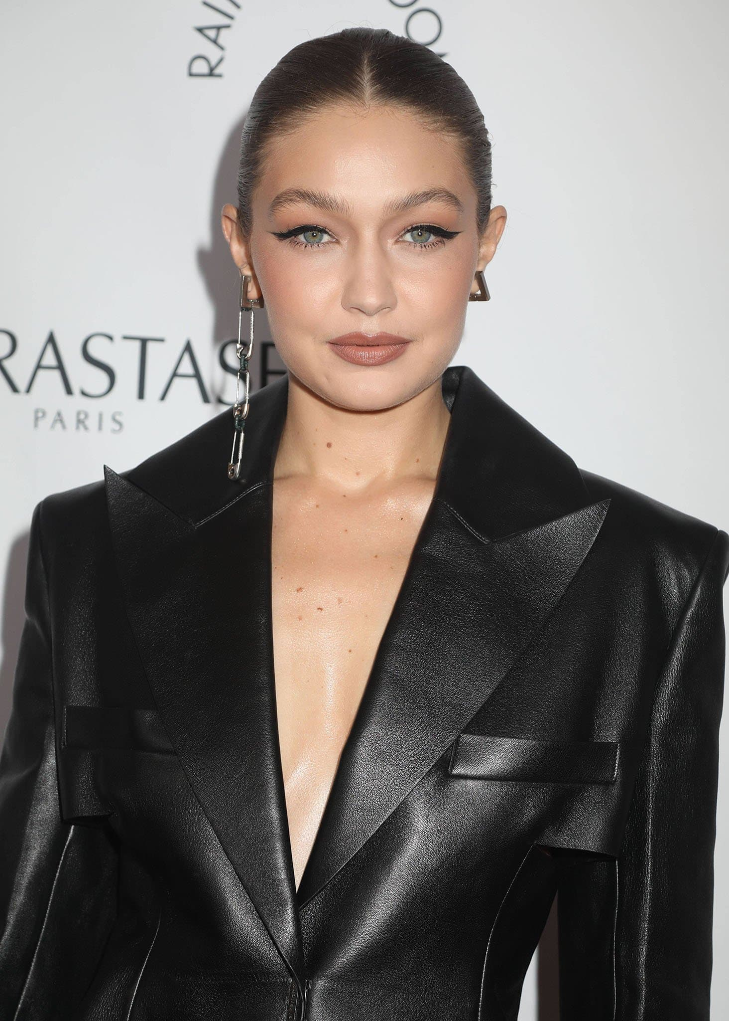 Gigi Hadid styles her hair in a slick braided ponytail and wears winged eyeliner and mauve lipstick