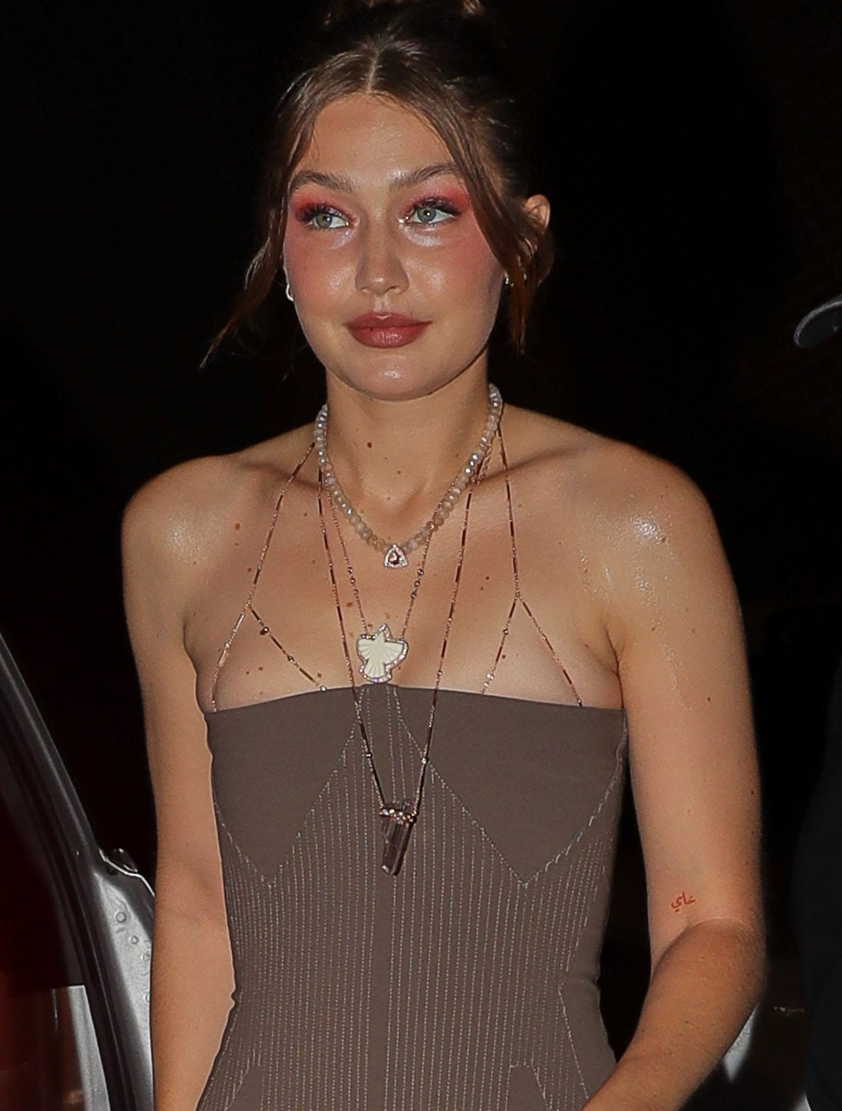 Gigi Hadid wears red smokey eye-makeup and styles her look with Jacquie Aiche layered necklaces