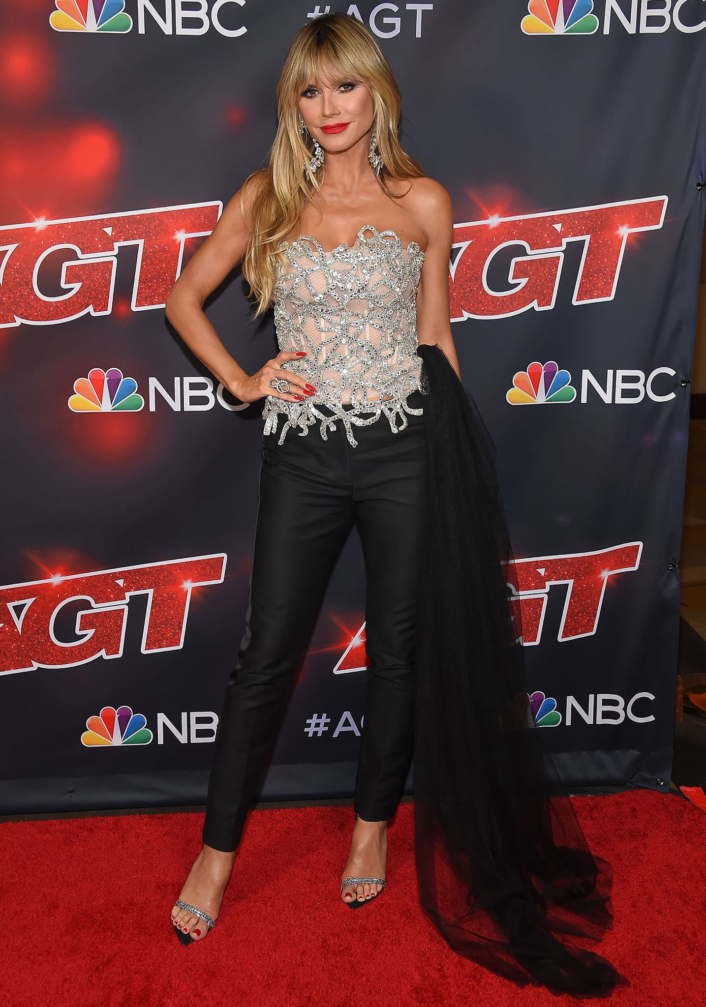 Heidi Klum wears an Oscar de la Renta corset-style top with slim-fit black trousers
