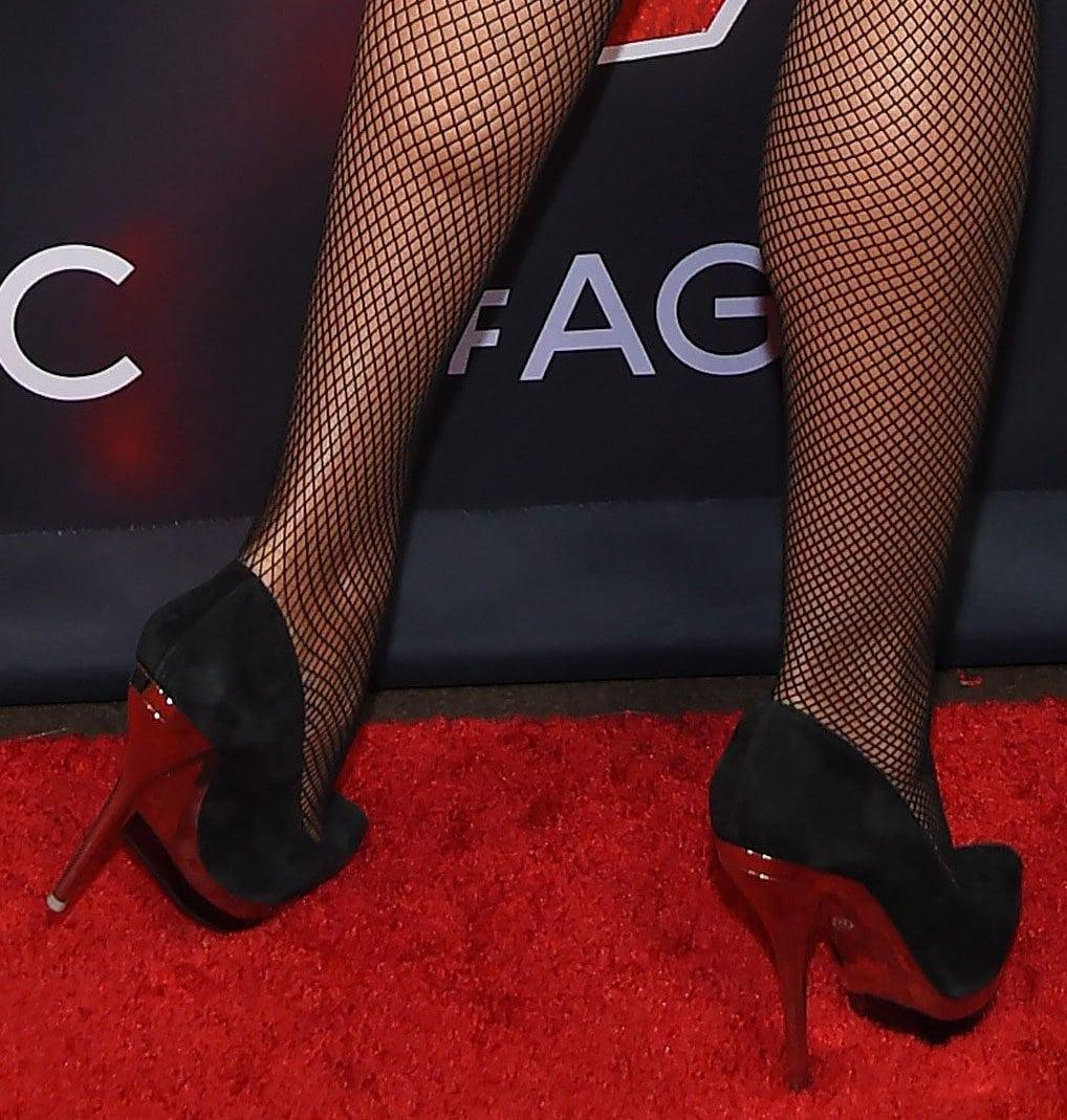 Heidi Klum pairs her mini dress with fishnets and mirror-heeled black pumps