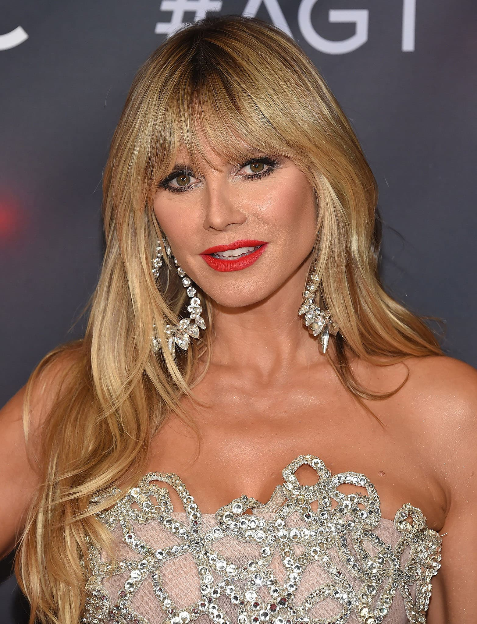 Heidi Klum wears her fringed hair down in soft waves with bold red lip color and glittery smokey eyeshadow