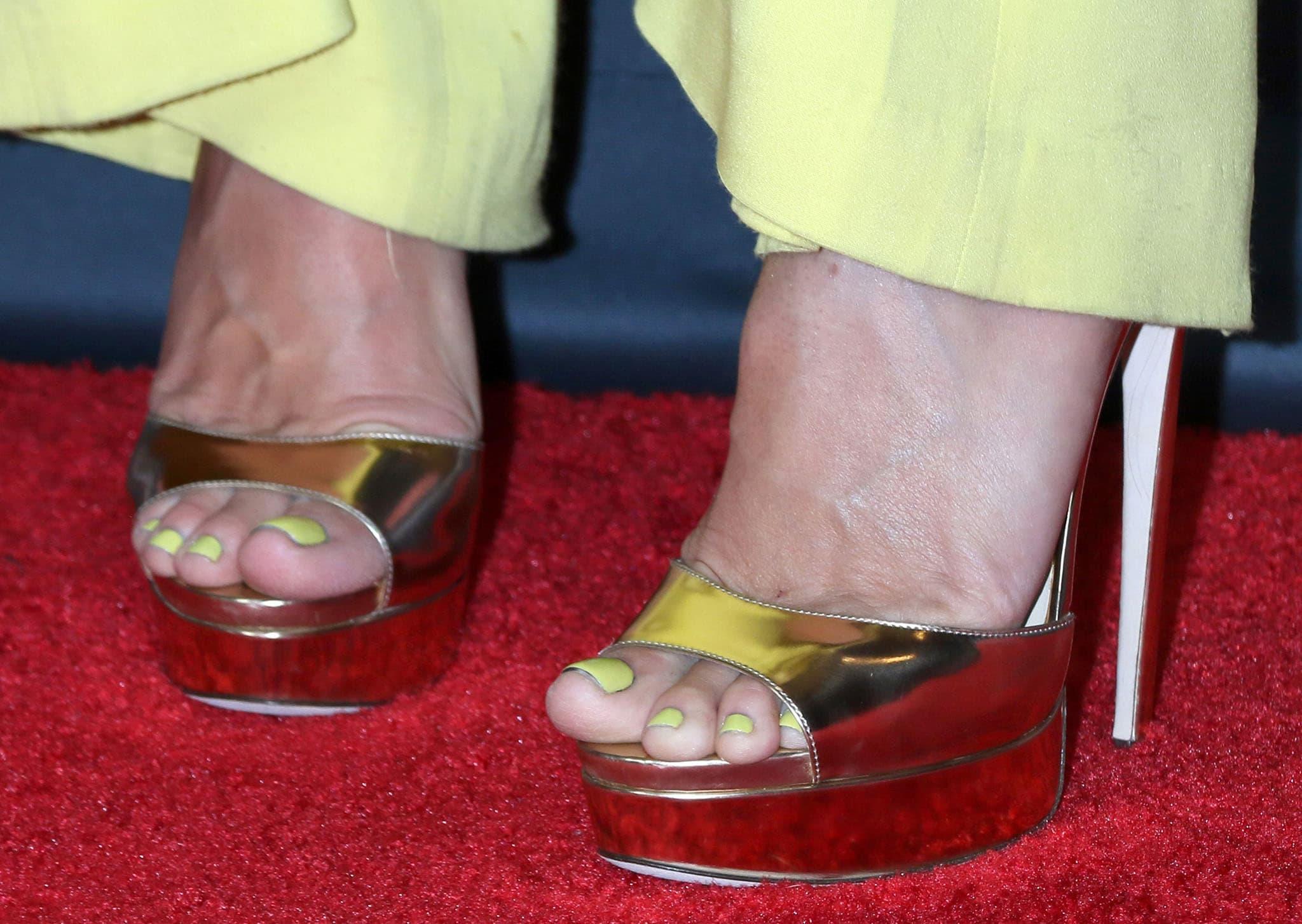 Heidi Klum displays her yellow pedicure in her mirror metallic gold platform sandals