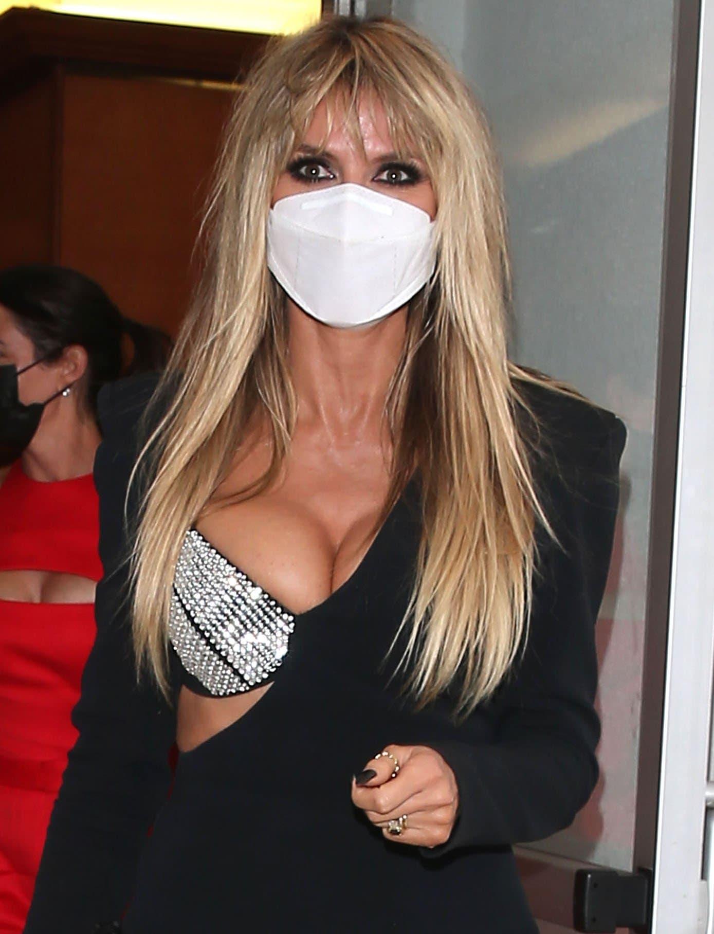 Heidi Klum wears her blonde hair straight and adds dramatic smokey eye-makeup to the look