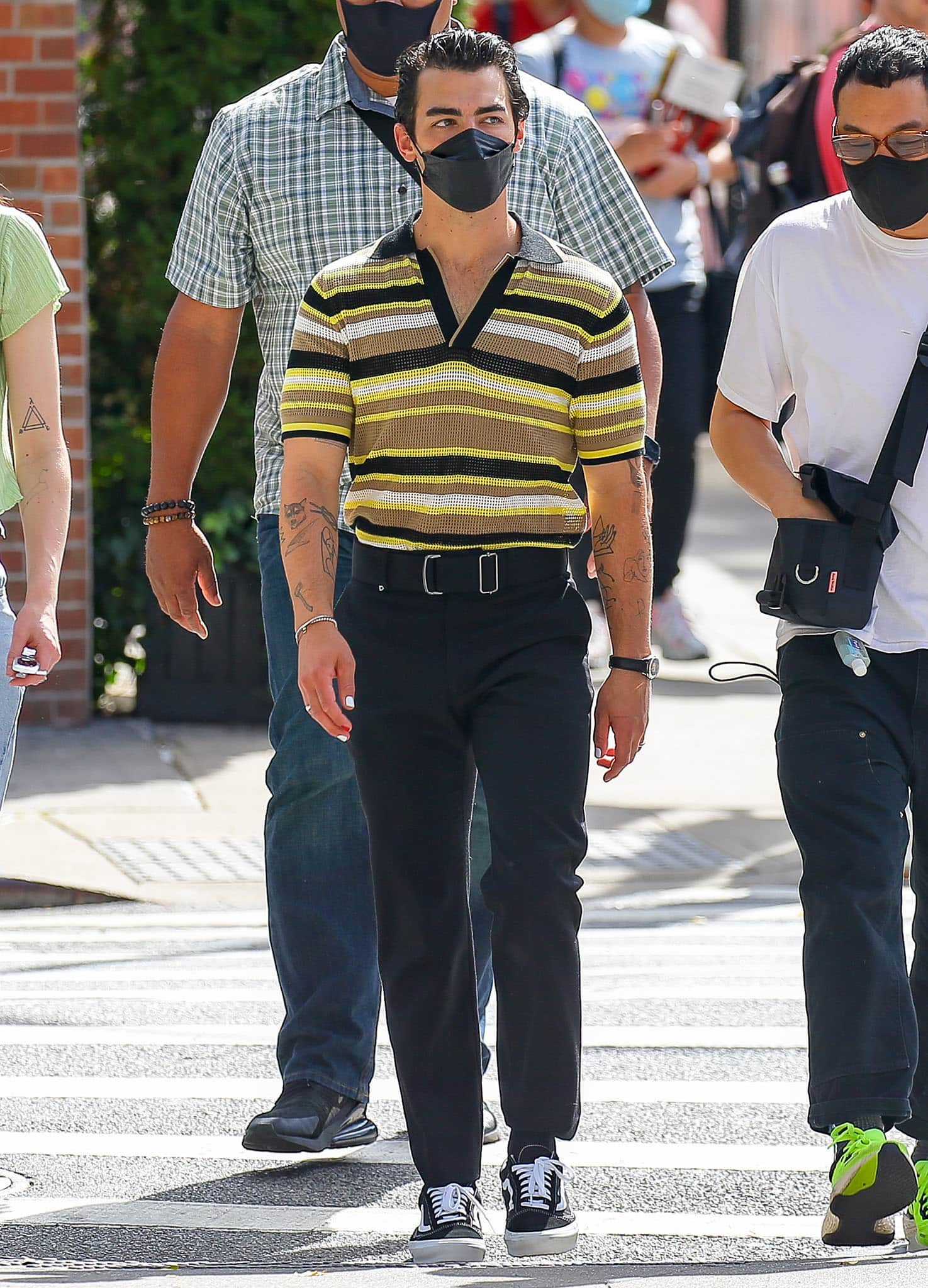 Joe Jonas coordinates with his wife in a throwback waffle knit striped top with black trousers and Vans sneakers