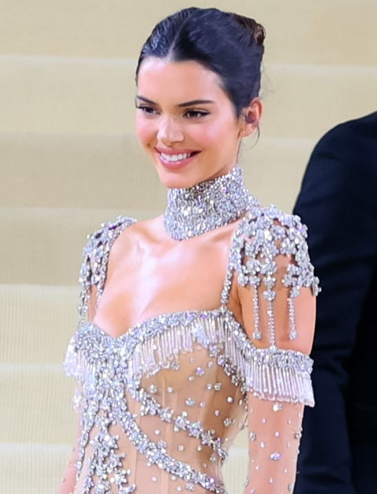 Kendall Jenner styles her hair into a midi-knot and wears simple makeup with winged eyeliner and rosy lip color