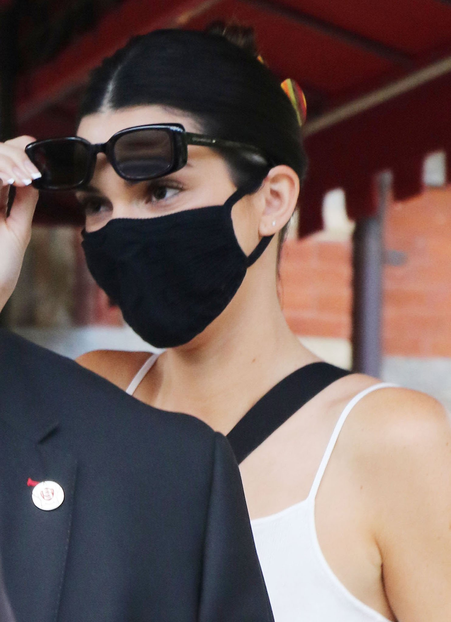 Kendall Jenner wears her tresses up and hides her face behind a face mask and black sunglasses