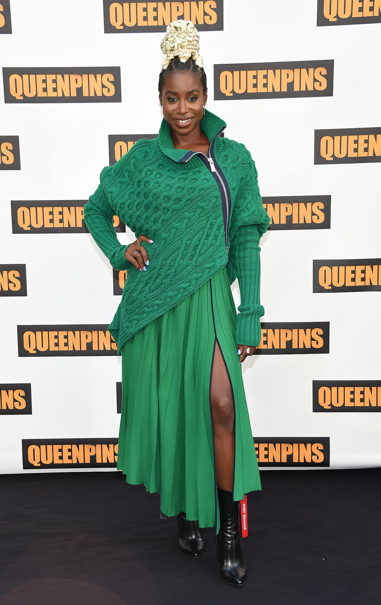 Kirby Howell-Baptiste wears a striking green sweater over a pleated dress
