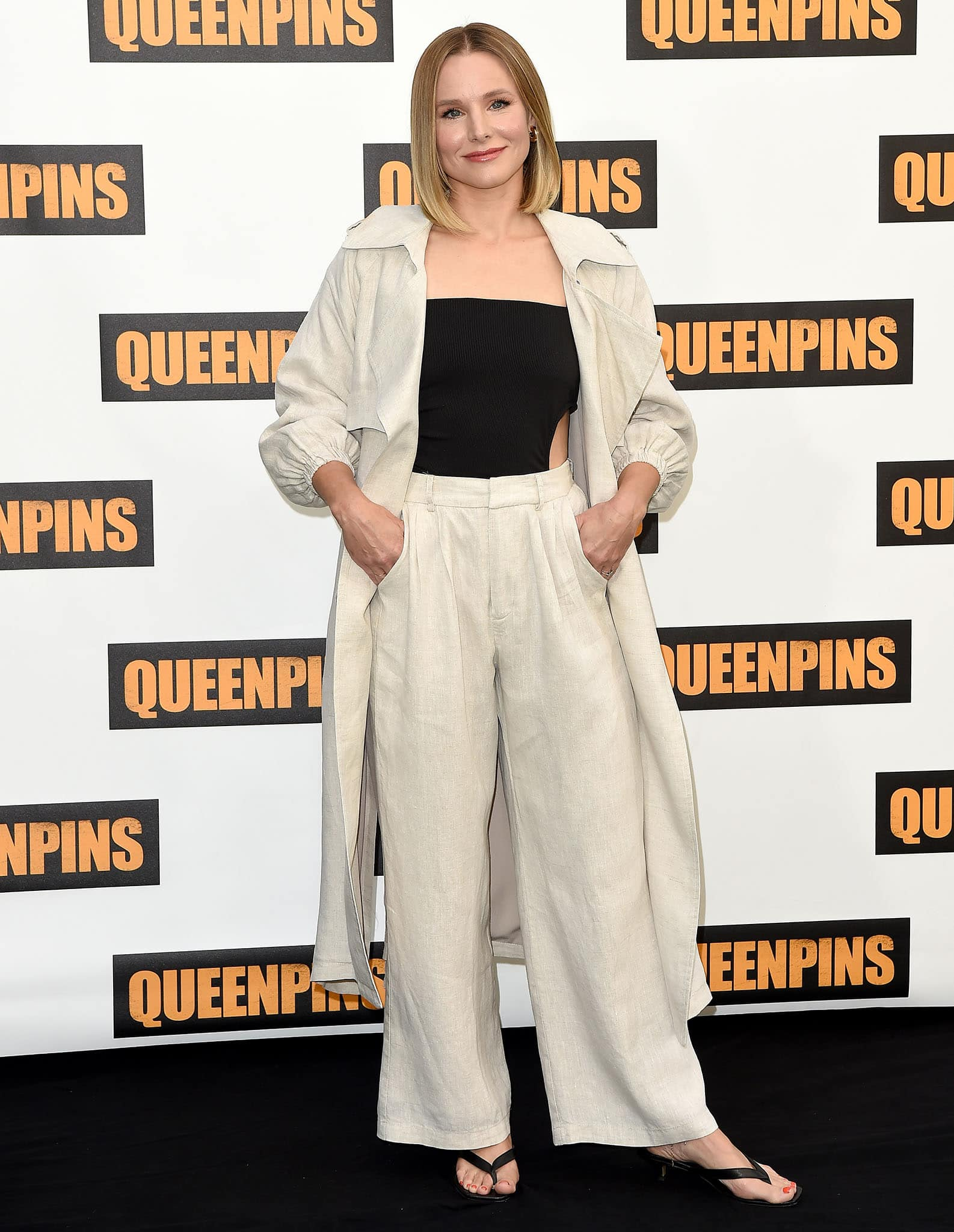 Kristen Bell wears a cutout bodysuit with linen pants and a duster coat