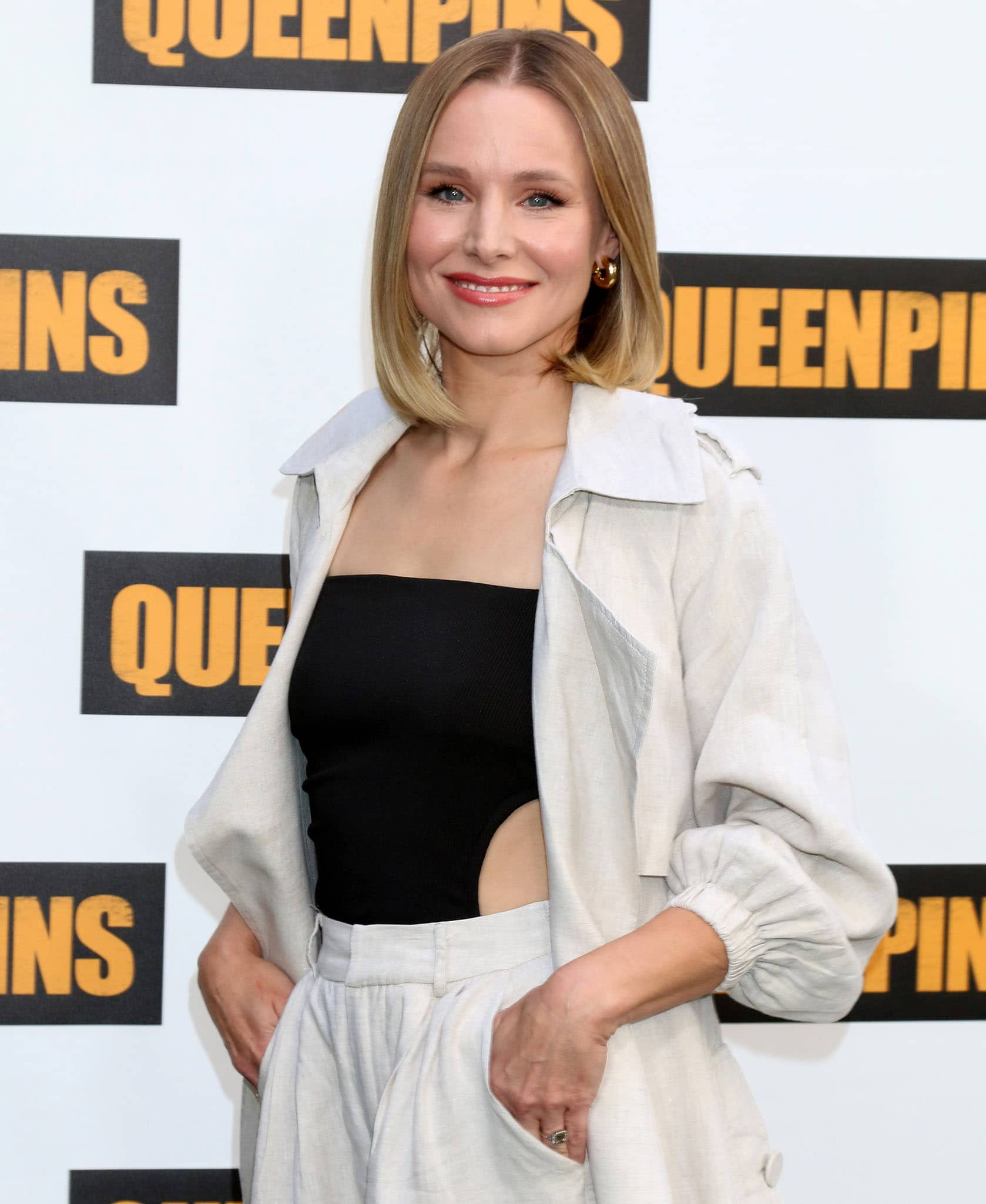 Kristen Bell wears her signature blunt bob hairstyle with soft pink makeup