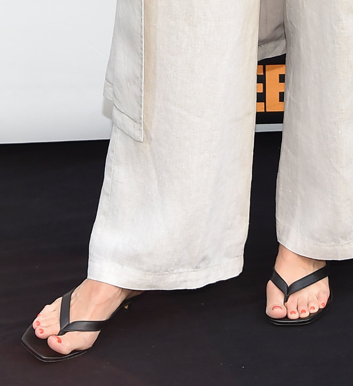 Kristen Bell shows off her red pedicure and feet in black thong square-toe sandals