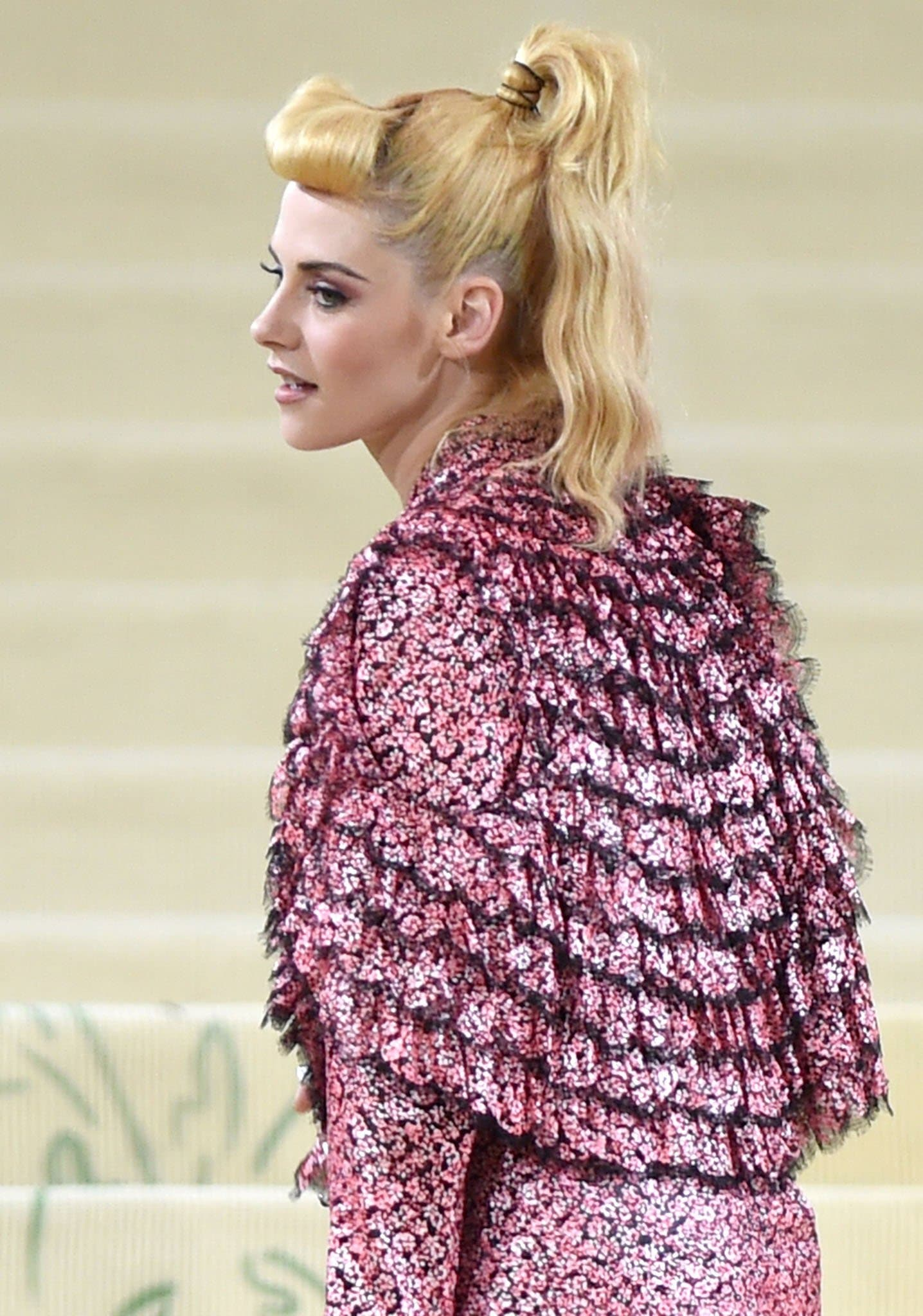 Kristen Stewart wears barbie pink smokey eye-makeup and styles her hair in a high ponytail with faux-fringe