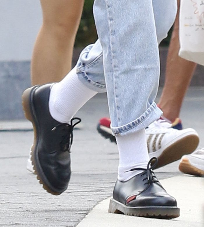 Kristen Stewart pairs her casual chic look with long white socks and Dr. Martens x Royal Mail shoes