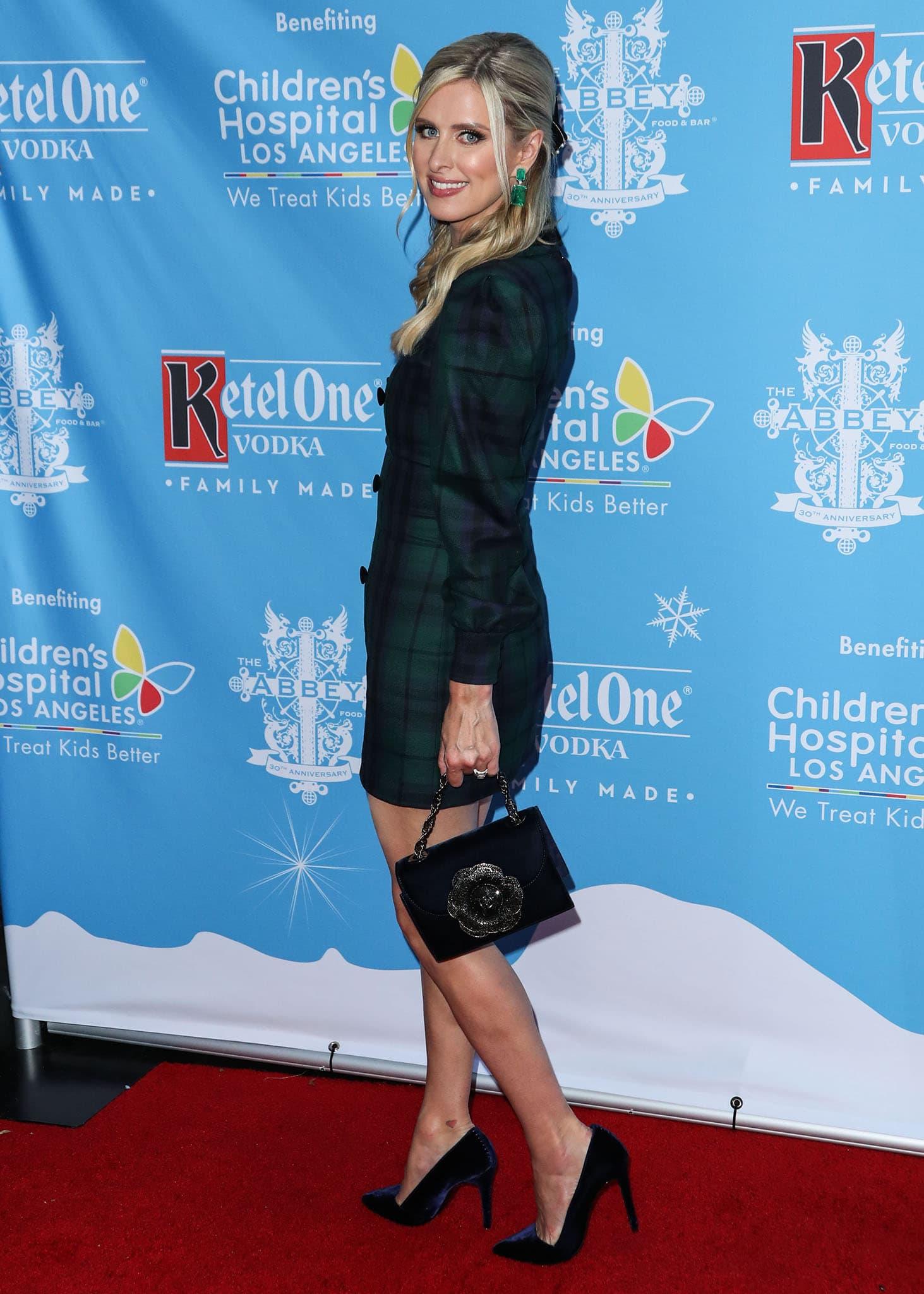 Nicky Hilton flaunts her slim legs in the plaid mini and carries a velvety Oscar de la Renta flower bag